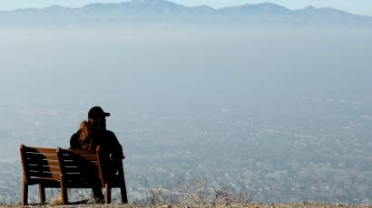 A man sits on a park bench and looks over the smog filled Salt Lake Valley in Draper, Uta