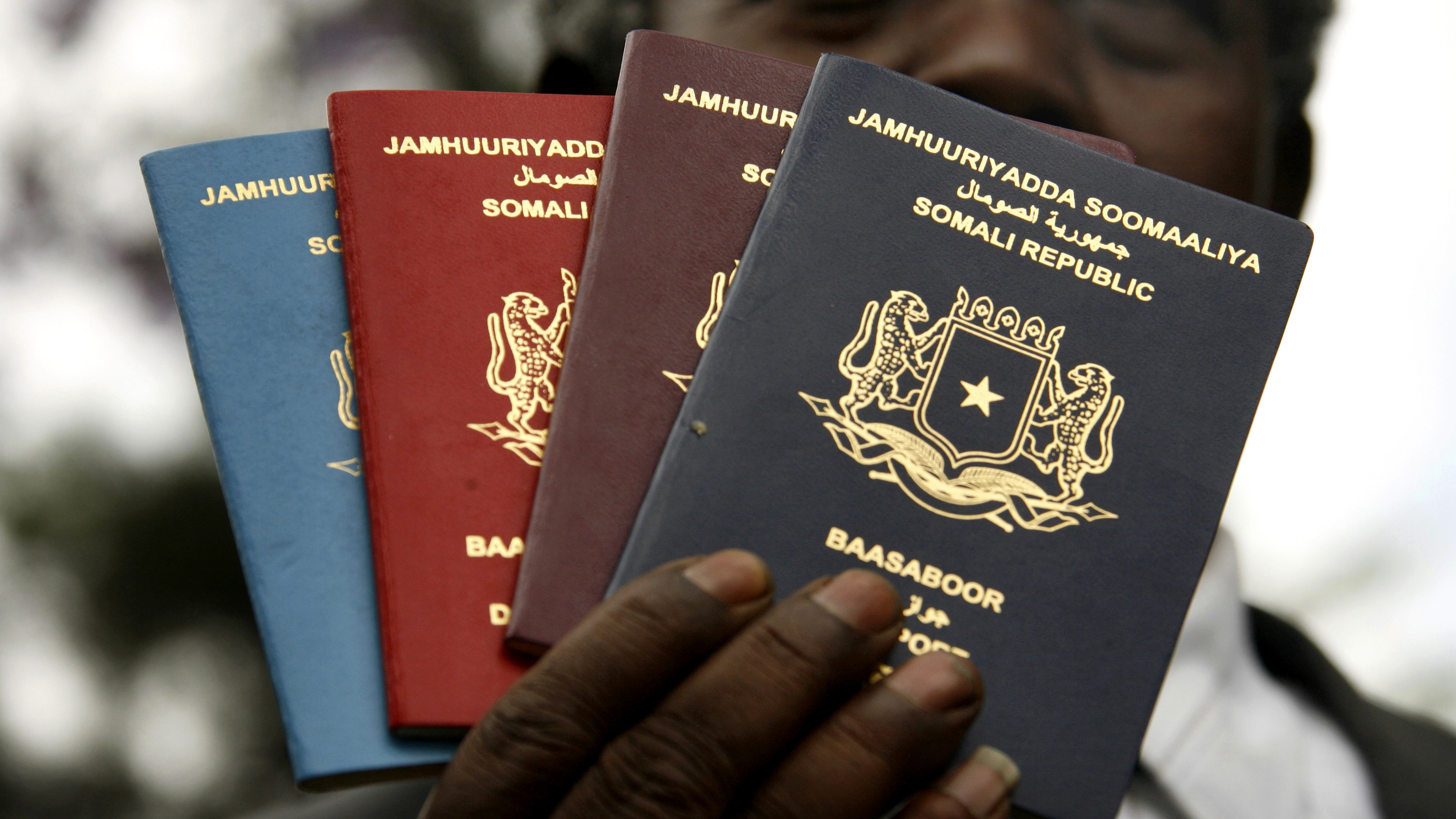 Abdullahi Gafow Mohamud, director of immigration for the transitional federal government of the Somali Republic, holds up new passports at the country's embassy in the Kenyan capital Nairobi, November 8, 2006. The Republic of Somalia is launching the new passports to meet international security standards and to prevent forgeries that were common with previous passports from the anarchic state on the Horn of Africa.  REUTERS/Finbarr O'Reilly (KENYA) - GM1DTWZJQUAA
