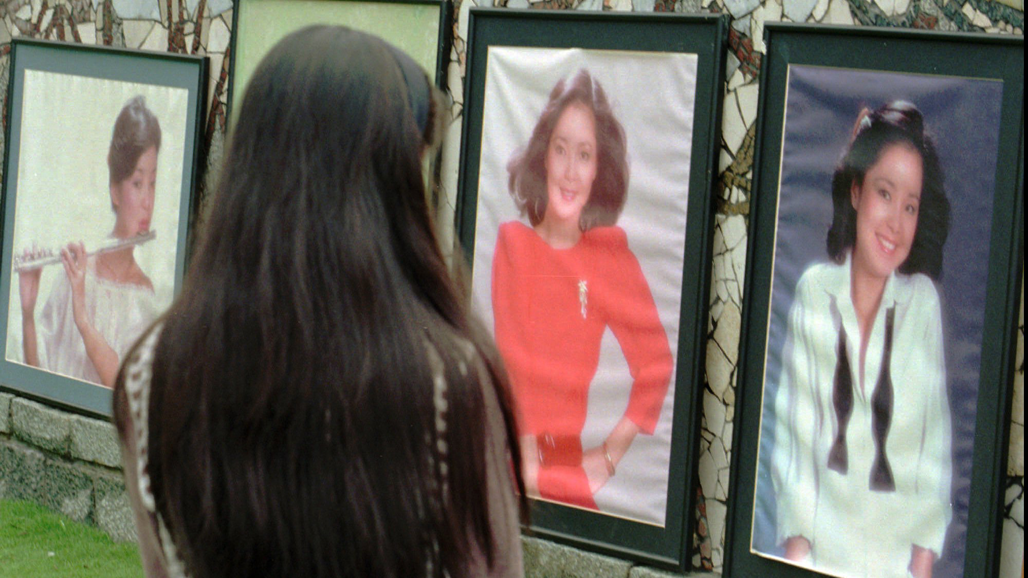 A fan of Taiwanese singer Teresa Teng views portraits set around her grave outside Taipei to mark the anniversary of Teng's death on May 8, 1996. Fans from Taiwan and Japan came to pay their respect to Teng, who died of asthma while on a trip to Thailand.