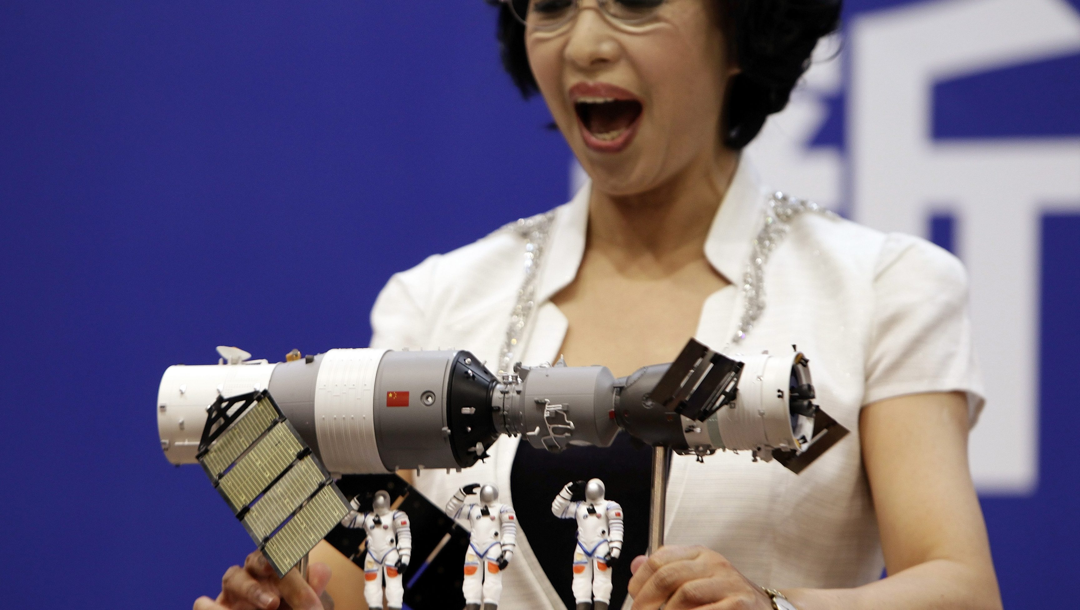 Spokeswoman for China's manned space program Wu Ping reacts as she shows a model of the Shenzhou-9 manned spacecraft,  the orbiting Tiangong-1 space lab module (L) and three Chinese astronauts during  a news conference at Jiuquan Satellite Launch Center, in northwest China's Gansu province, June 15, 2012. The Shenzhou-9 manned spacecraft will be launched at 18:37 (10:37 GMT) on June 16, 2012, according to a decision made by China's manned space docking program headquarters, Xinhua News Agency reported. REUTERS/Jason Lee (CHINA - Tags: SCIENCE TECHNOLOGY) - GM2E86F18YS01