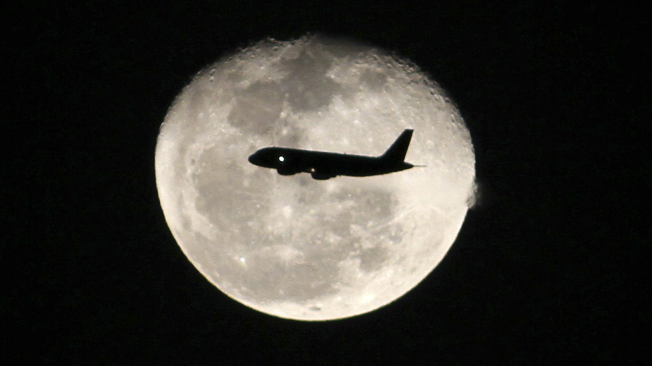 A passenger jet flies in front of the moon in Bogota