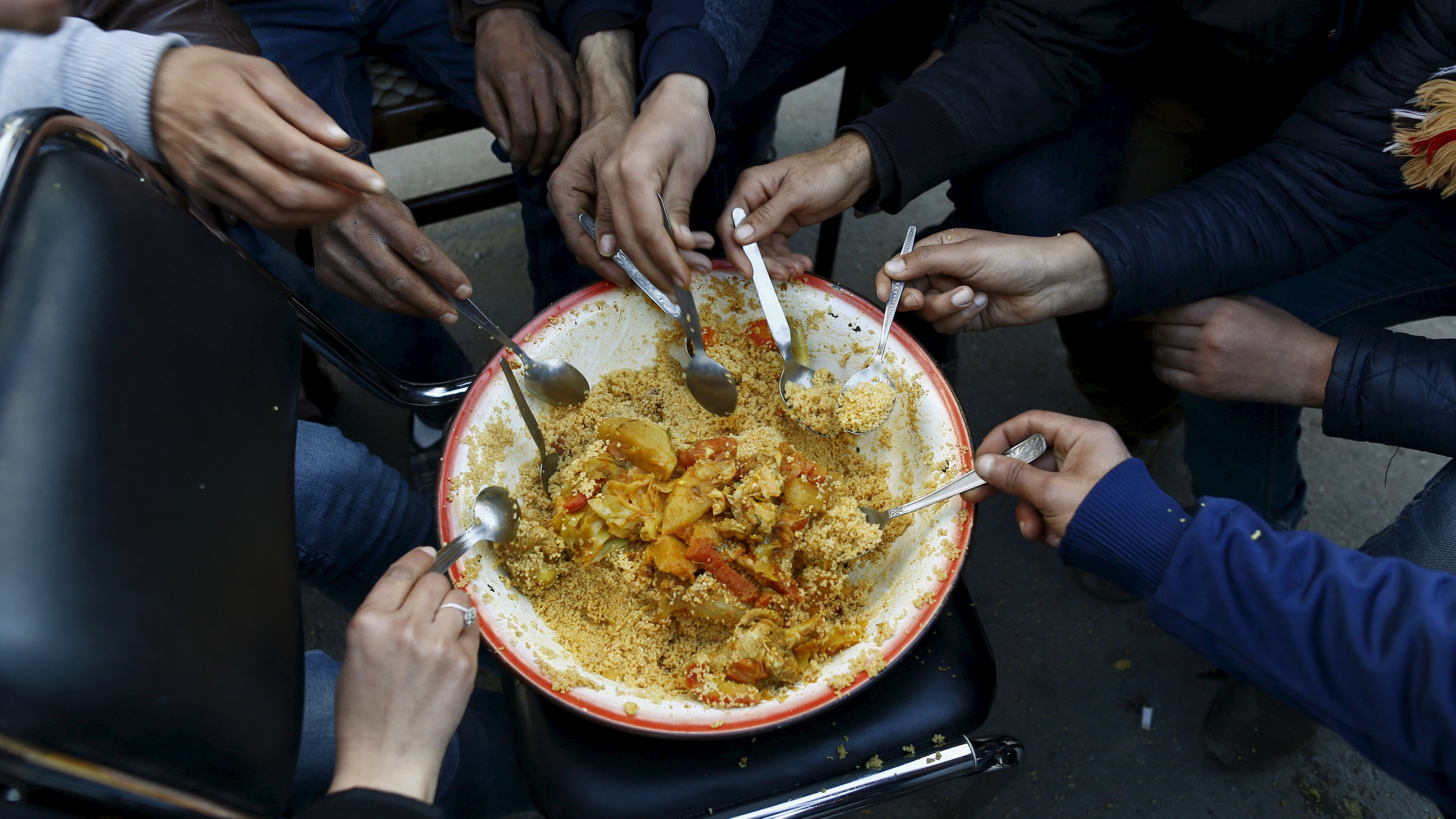 Unemployed graduates eat couscous as they hold a sit-in protest to get jobs, at the local government office premises in Kasserine, Tunisia, January 26, 2016. The protest is part of demonstrations which began last week after a young man killed himself after apparently being refused a public job. REUTERS/Zohra Bensemra - GF20000108029
