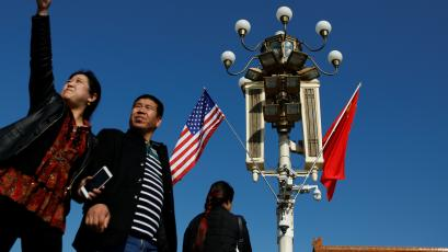 People pass under a pole with security cameras, U.S. and China's flags near the Forbidden City ahead of the visit by U.S. President Donald Trump to Beijing, China November 8, 2017.