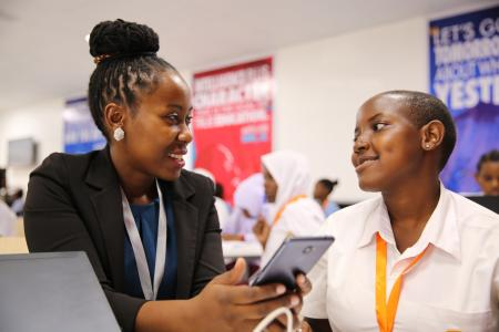 Carolyne Ekyarisiima inspecting the mobile app developed by one of the young coders at the Entrepreneurship Summit.