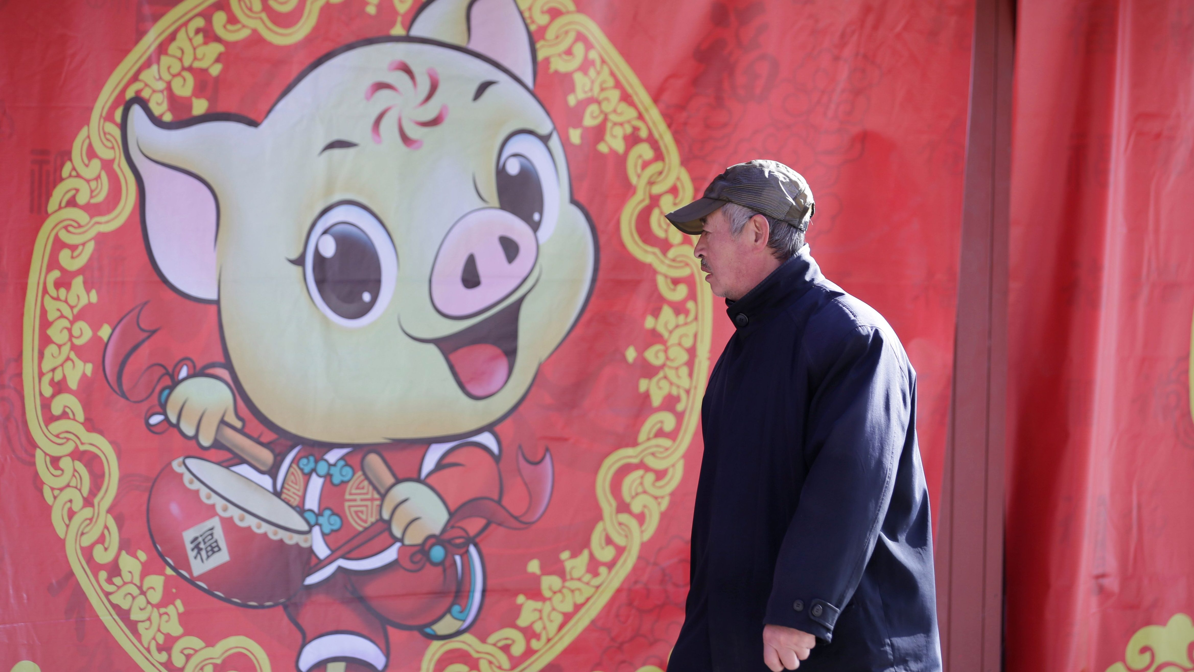 A man walks past a poster celebrating the upcoming Lunar New Year of the Pig at Ditan Park in Beijing, China January 28, 2019.