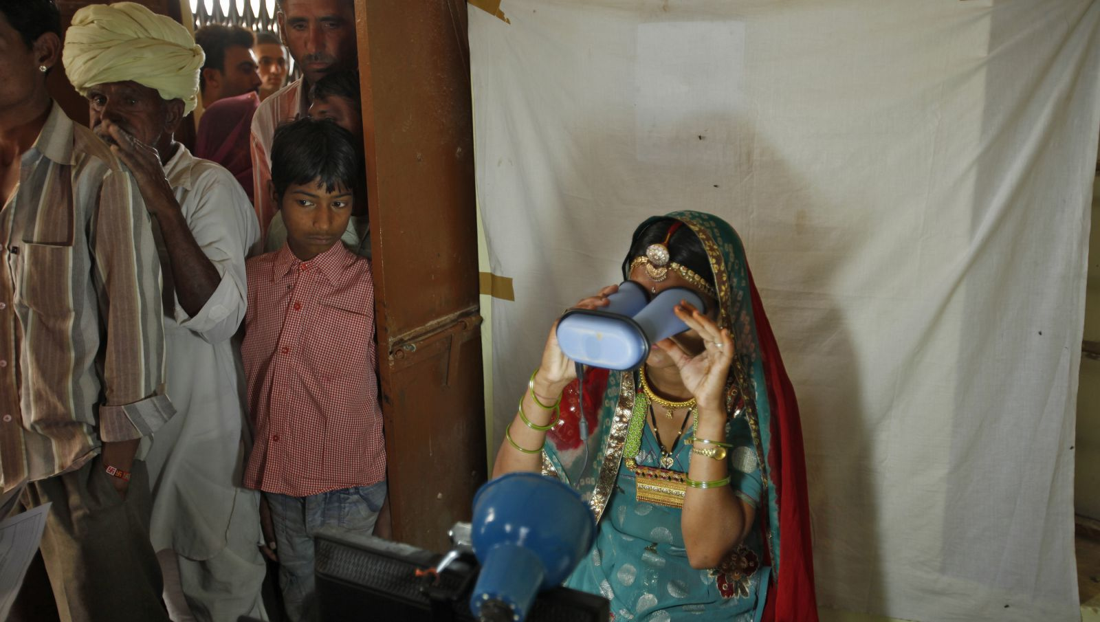 A villager goes through the process of eye scanning for Unique Identification (UID) database system at an enrolment centre at Merta district in the desert Indian state of Rajasthan February 21, 2013.In a more ambitious version of programmes that have slashed poverty in Brazil and Mexico, the Indian government has begun to use the UID database, known as Aadhaar, to make direct cash transfers to the poor, in an attempt to cut out frauds who siphon billions of dollars from welfare schemes. Picture taken February 21, 2013