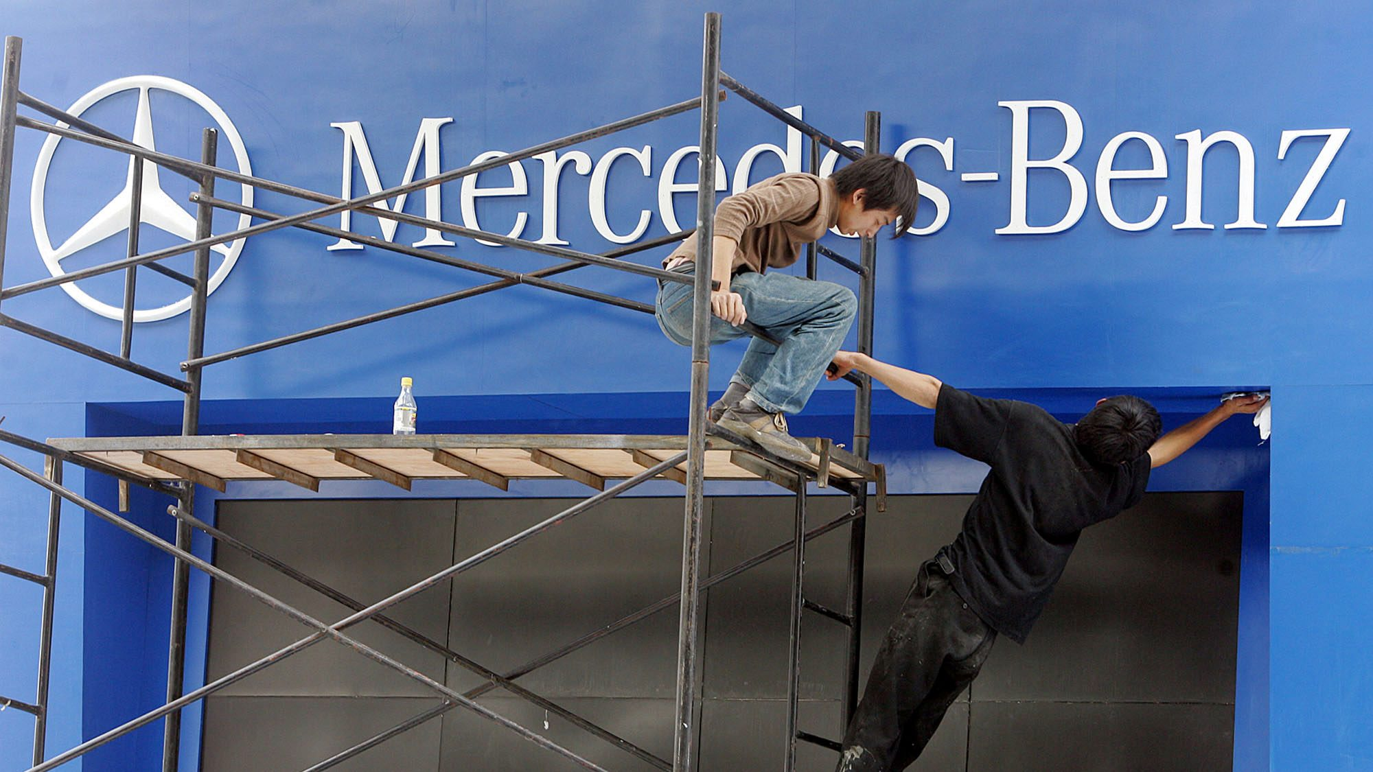 Chinese workers prepare sign of Mercedes-Benz, one of the popular cars among Chinese new wealthy upper class, Wednesday April 20, 2005 at an auto show in Shanghai, China. The Chinese economy grew by 9.5 percent in the fourth quarter of 2004 from a year earlier. The government's official target for growth is 8 percent a year.
