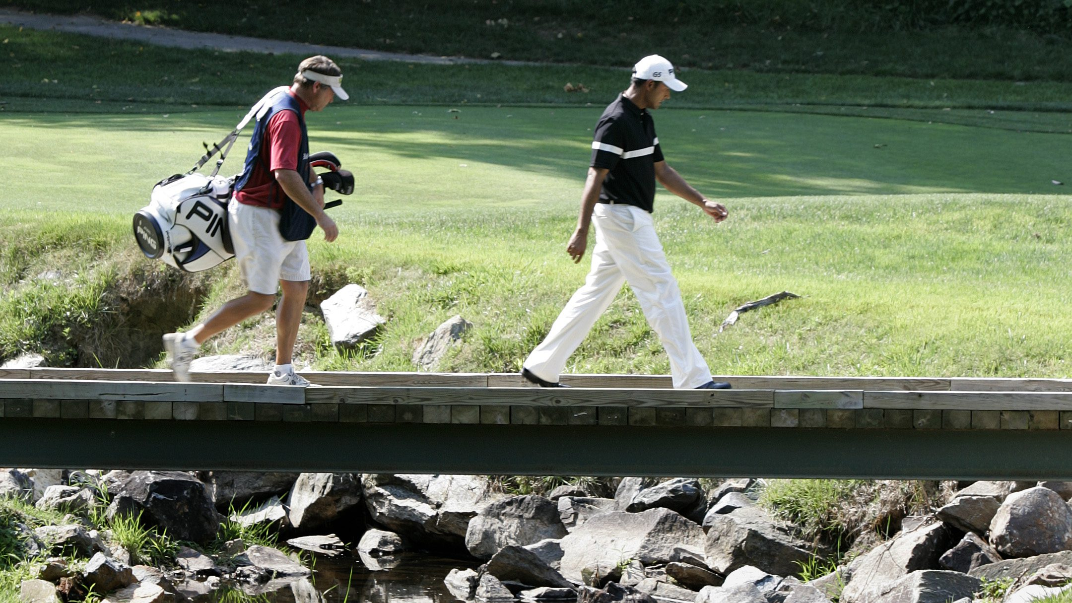 Golfer Arjun Atwal, right, of Calcutta, India, walks with his caddie as they cross a river that runs through the 12th fairway during the first round of the Booz Allen Classic at TPC Avenel in Potomac, Md., Thursday, June 22, 2006. (AP Photo/Chris Gardner)