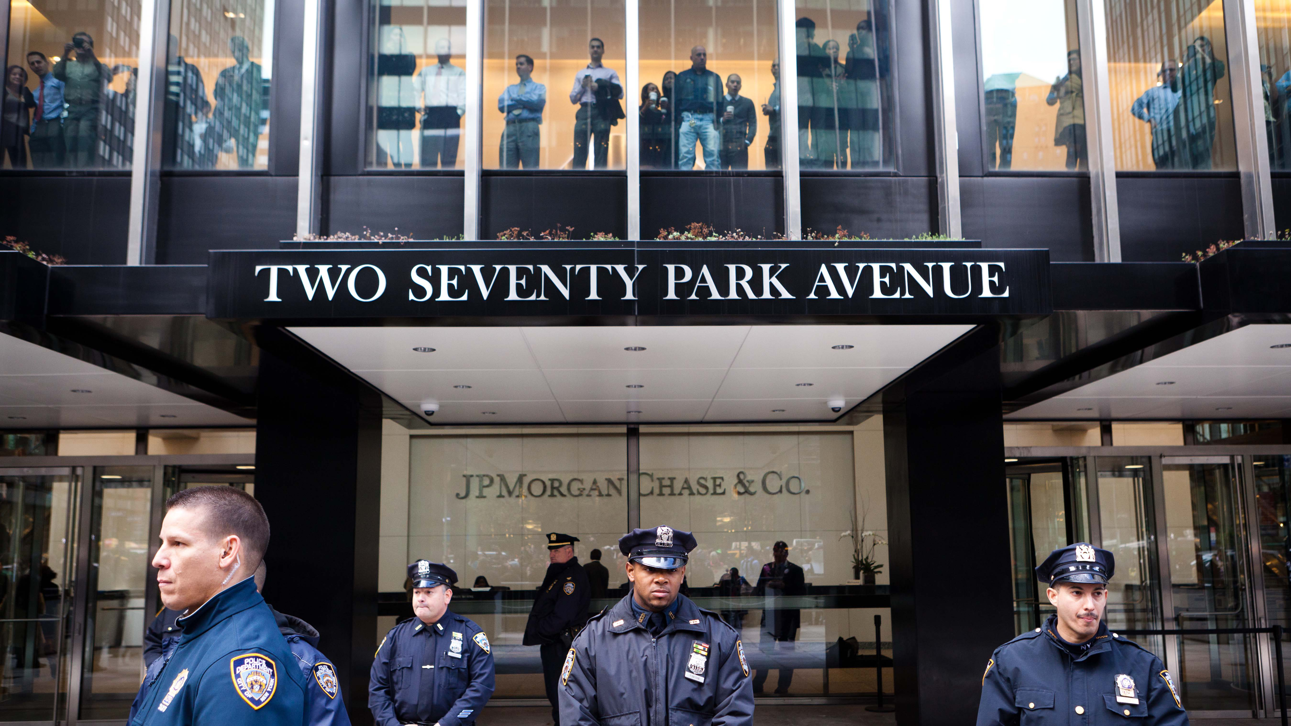 Police officers stand guard as employees look out from inside at marching Occupy Wall Street protestors near the JP Morgan Chase corporate headquarters on Park Avenue in New York on Friday, Oct. 28, 2011. Nearly 400 OccupyWallStreet protesters carried what they said were 7,000 letters of complaint to offices of banks they accuse of corporate greed. (AP Photo/John Minchillo)