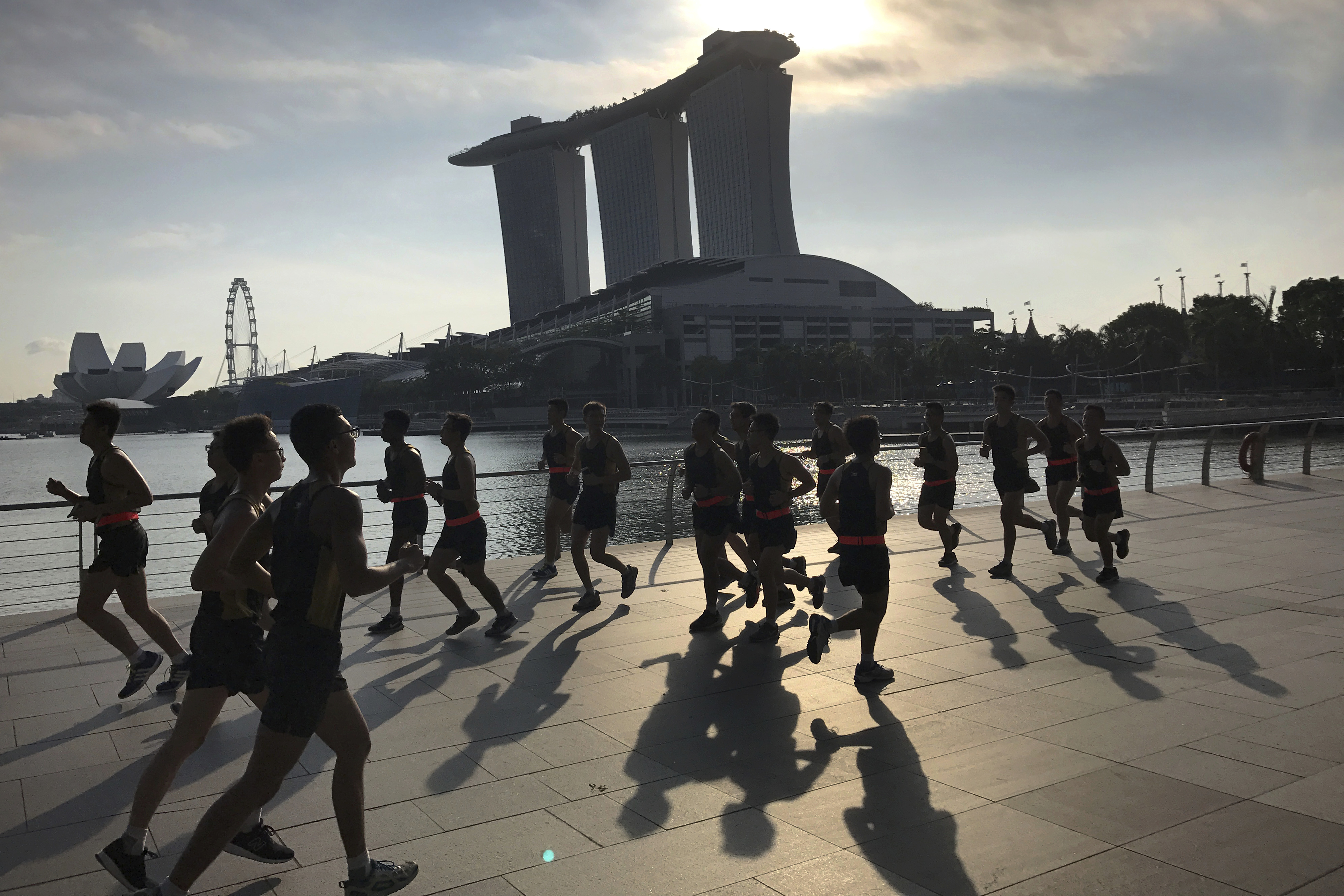Runners are seen in silhouette and their shadows cast on the Marina Bay promenade as they jog at the start of a work day on Friday Aug. 4, 2017, in Singapore. The Marina Bay Sands hotel towers, right, ArtScience Museum, left, and Singapore Flyer, second left, are seen in the background.