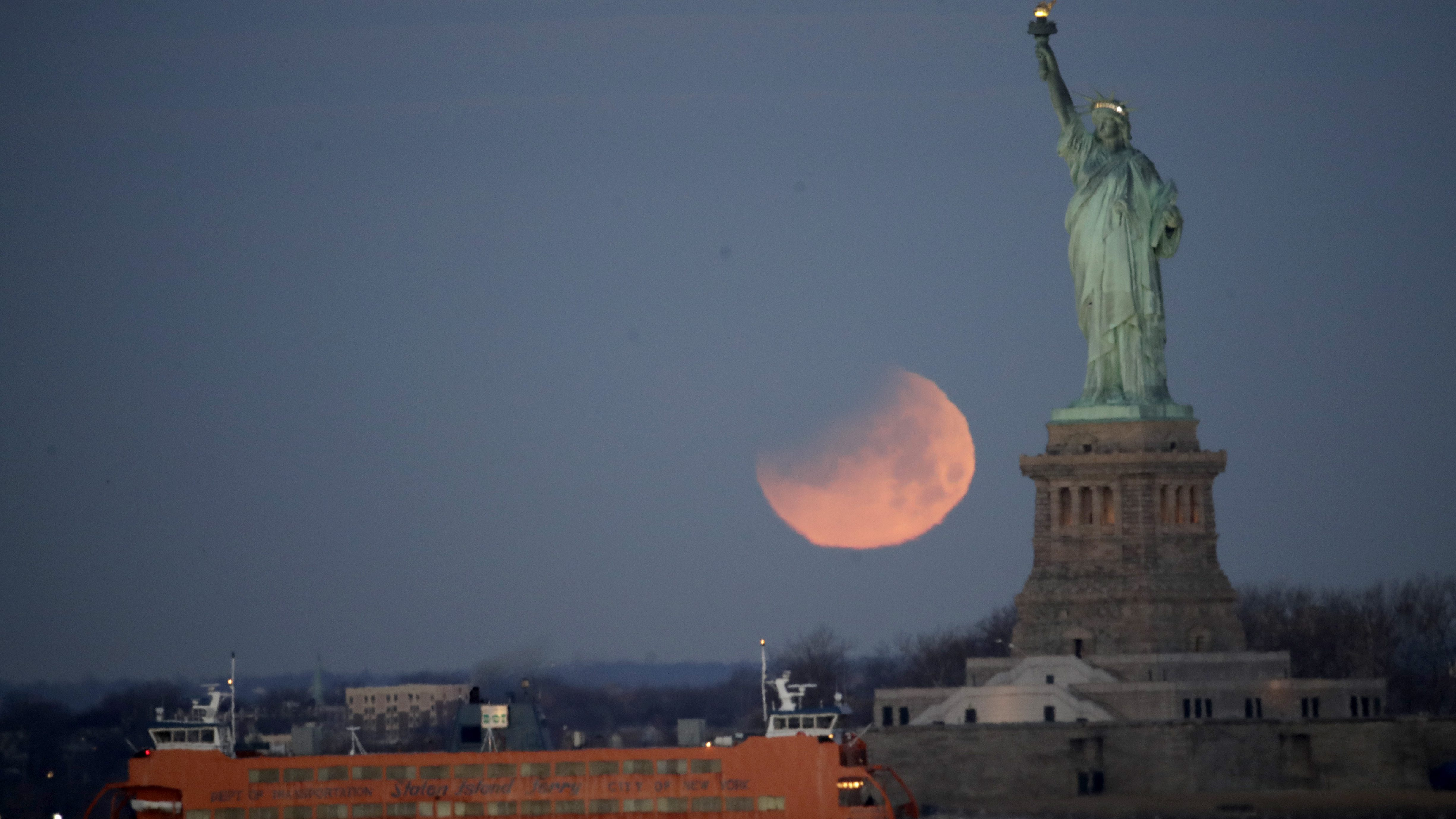 The Statue of Liberty and the Staten Island Ferry are backdropped by a supermoon, Wednesday, Jan. 31, 2018, seen from the Brooklyn borough of New York. The supermoon, which is the final of three consecutive supermoons, also experience lunar eclipse as it set over the horizon, but only a partial eclipse was visible in the East Coast. (AP Photo/Julio Cortez)