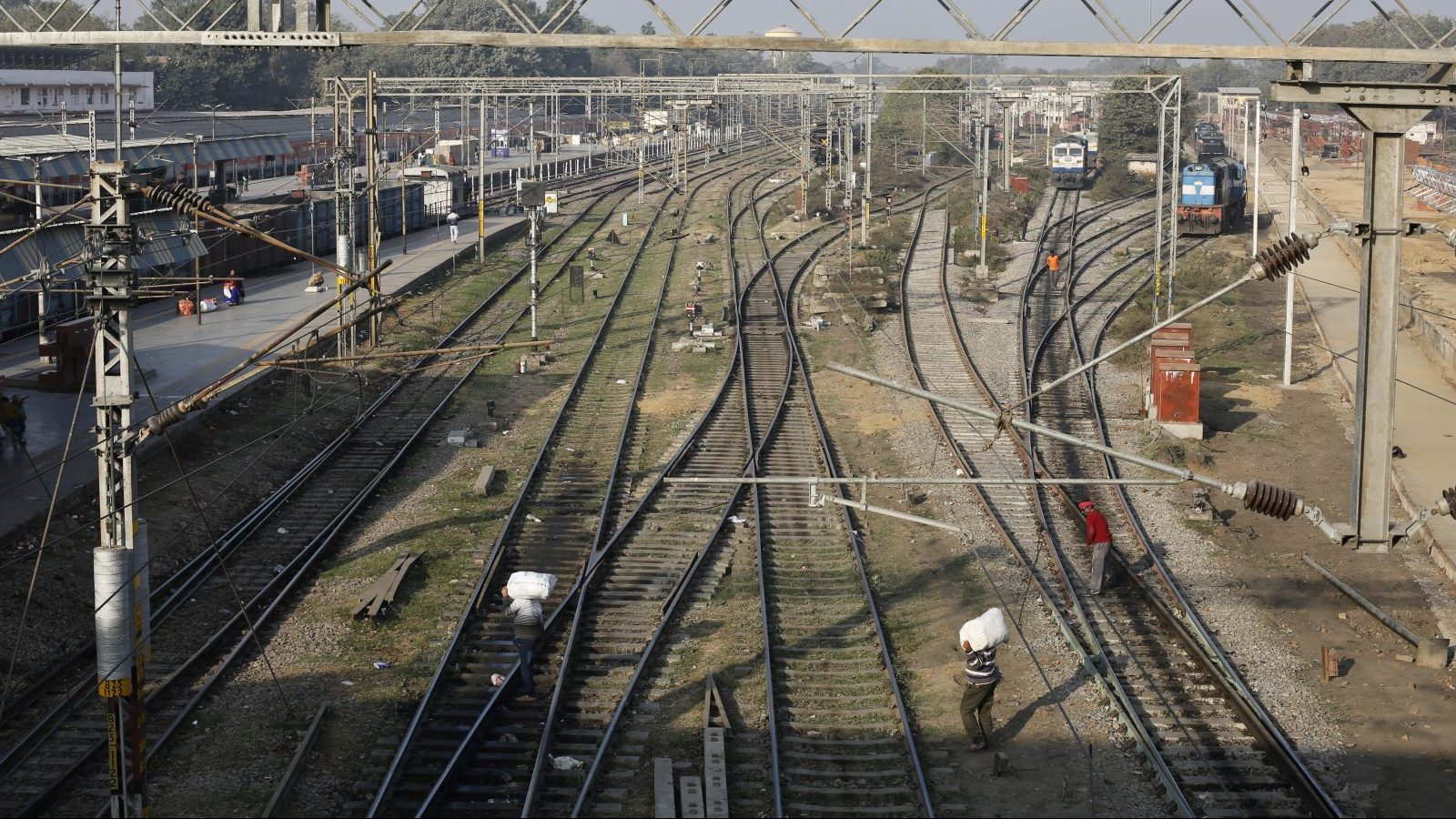 Indian passengers cross railway tracks at a junction train station in Allahabad, India, Thursday, Feb. 1, 2018. India's finance minister has announced a federal budget with a string of populist giveaways, from free cooking gas connection to a health plan for the poor, in an attempt to woo voters ahead of national elections next year. (AP Photo/Rajesh Kumar Singh)