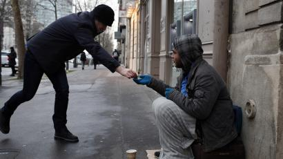 A homeless receives some money as he sits in the streets in Paris.