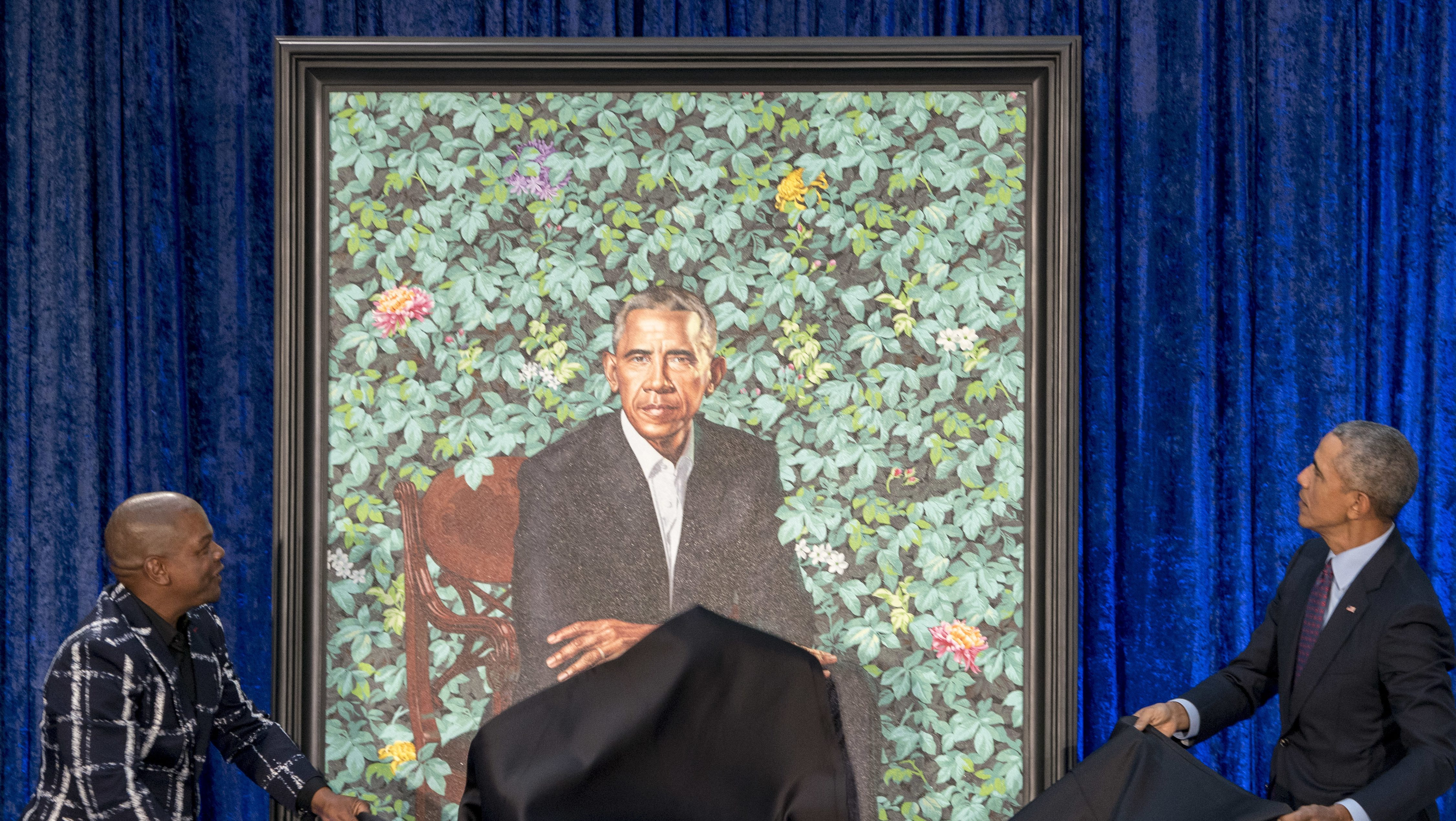 Former President Barack Obama, right, and Artist Kehinde Wiley, left, unveil Obama's official portrait at the Smithsonian's National Portrait Gallery, Monday, Feb. 12, 2018, in Washington.
