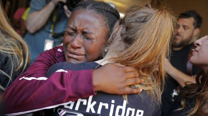 Marla Eveillard, 14, cries as she hugs friends before the start of a vigil at the Parkland Baptist Church, for the victims of the Marjory Stoneman Douglas High School shooting.