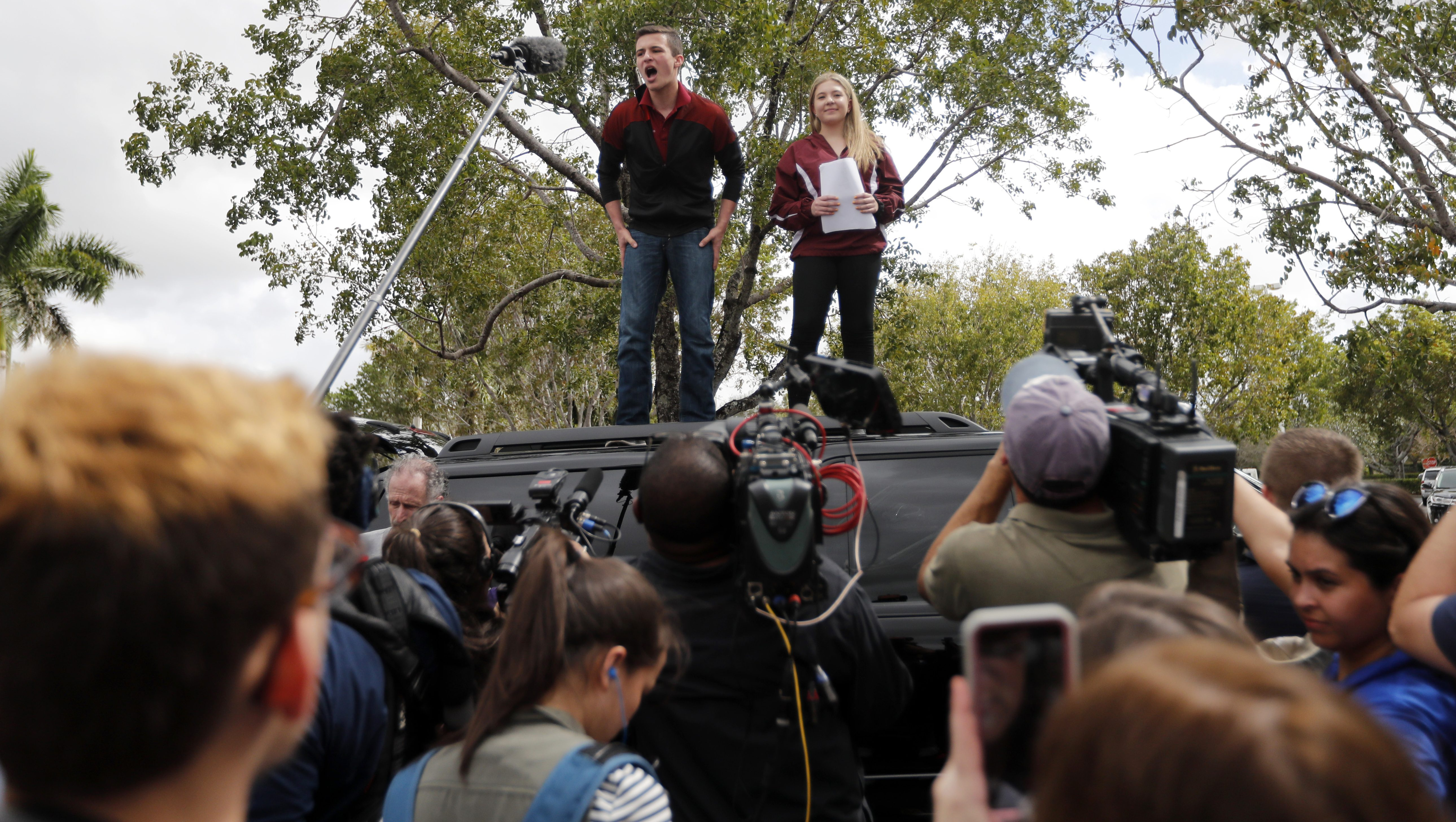 Organizers Cameron Kasky, left, and Jackie Corin, student survivors from Marjory Stoneman Douglas High School address fellow students before boarding buses in Parkland, Fla., Tuesday, Feb. 20, 2018, to rally outside the state capitol.   The students plan to hold a rally Wednesday in hopes that it will put pressure on the state's Republican-controlled Legislature to consider a sweeping package of gun-control laws, something some GOP lawmakers said Monday they would consider. (AP Photo/Gerald Herbert)