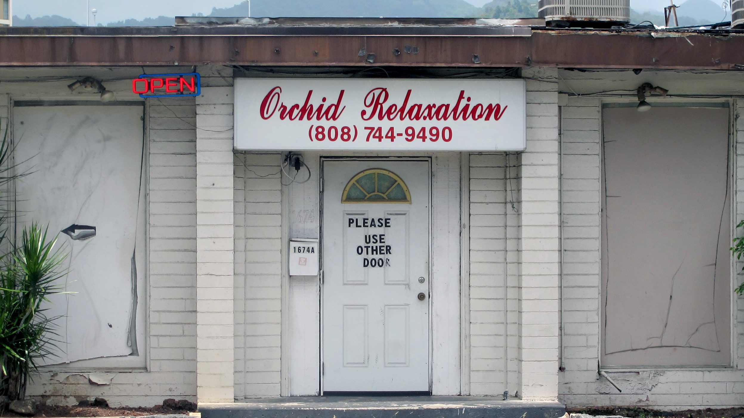 An open sign hangs outside Orchid Relaxation in Honolulu, Wednesday, May 6, 2015. The massage parlor was one of several local businesses that were targeted in a police prostitution sting over the weekend. Officers used an unusual tactic charging the women with sexual abuse, a more serious crime, according to legal experts and advocates for prostitutes. (AP Photo/Jennifer Sinco Kelleher)