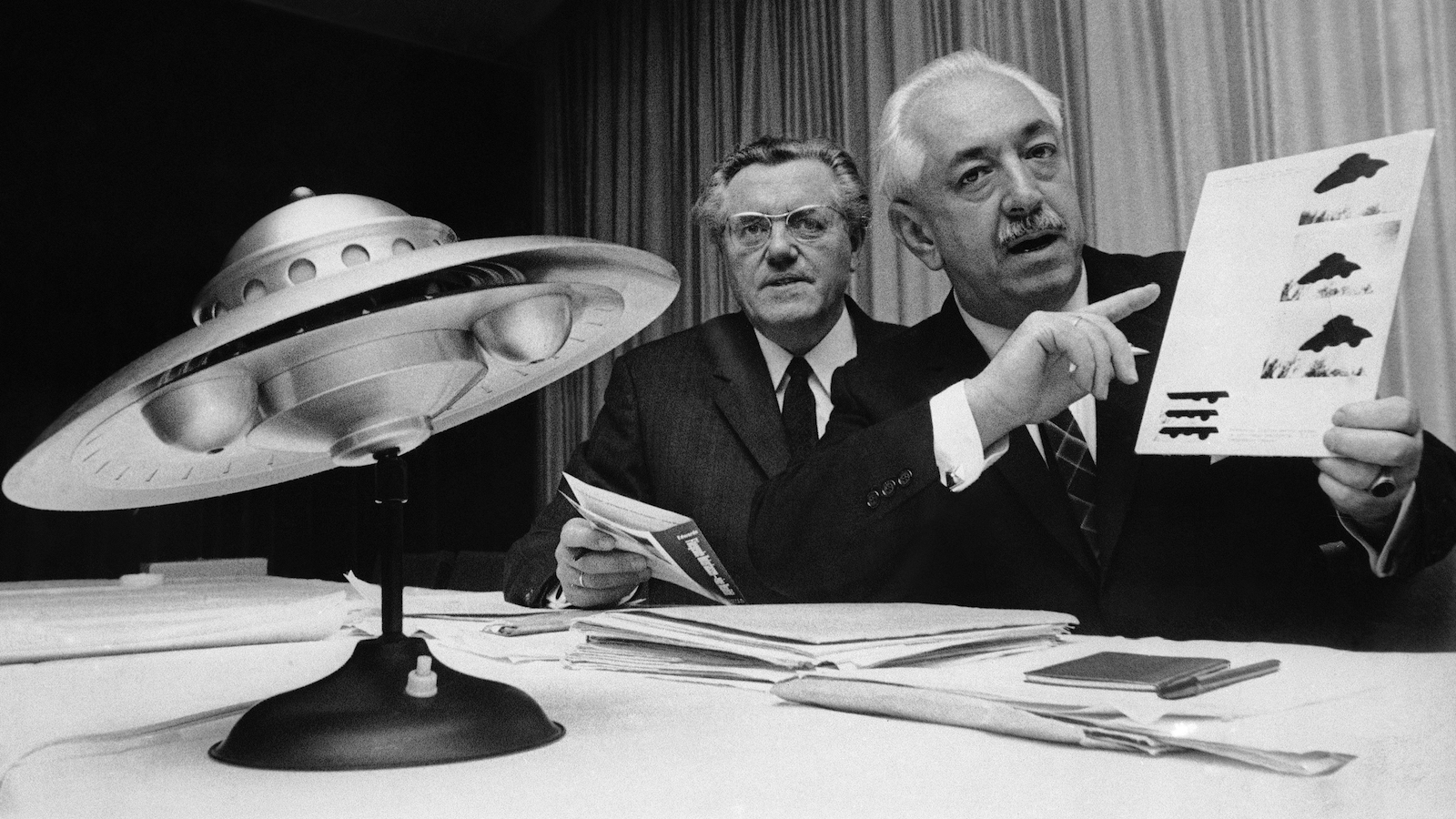 World reception center for official visitors from outer space was proposed by an American specialist on unidentified flying objects (UFOs). Hungarian-born Colman von Keviczky, a former United Nations official, right, and Karl L. Viet, the president of the German branch of the UFO study society, are at a news conference on the international conference of UFO-students, Oct. 31, 1967 in Mainz, Germany. At foreground is a model of a UFO which doubles as bedside lamp.  (AP Photo/Kurt Strumpf)