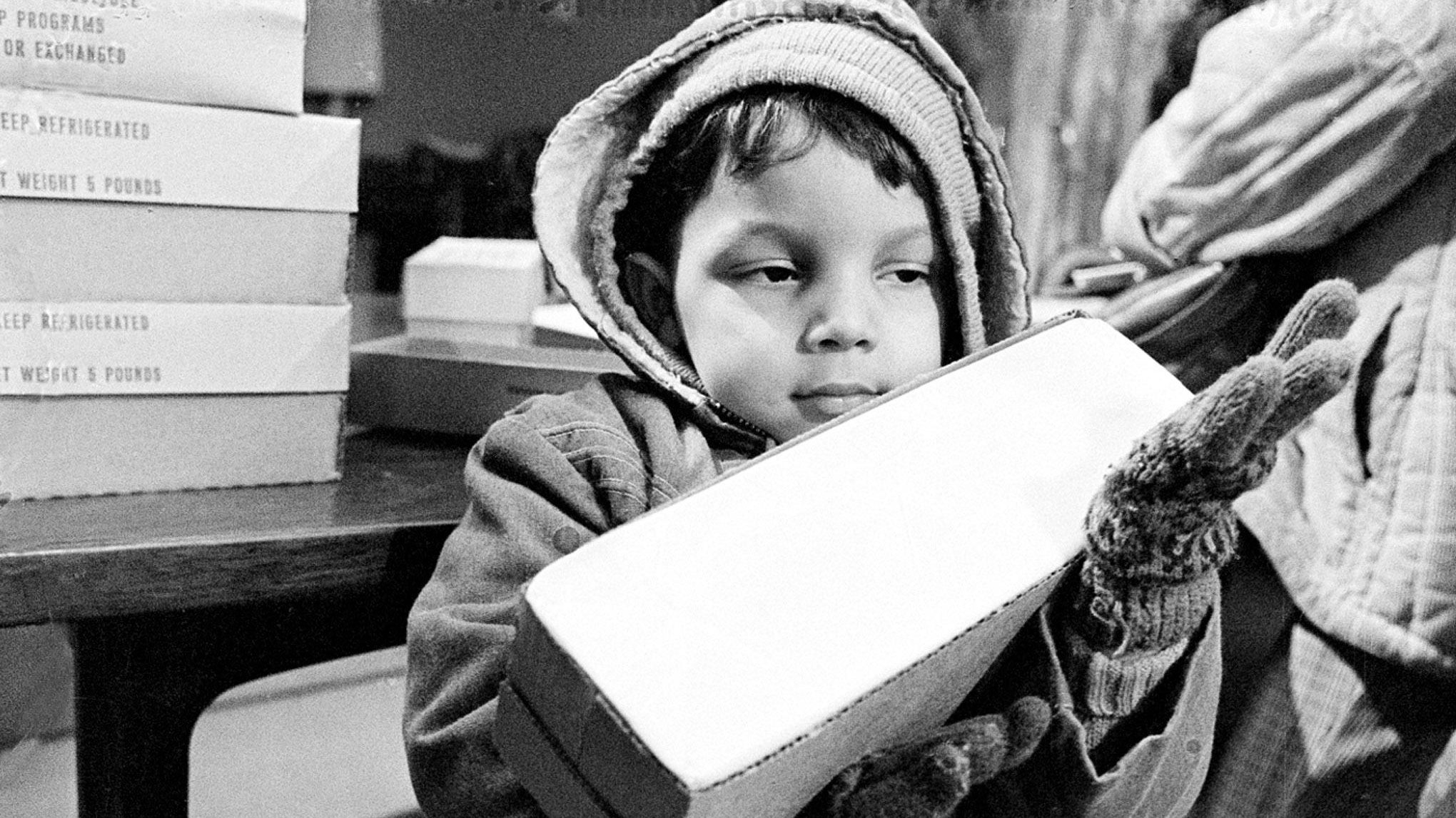 ** FILE ** In this Feb. 16, 1982, file three-year-old Michael Quinones has a little problem handling the free 5-pound package of processed American cheese his mother received as part of a U.S. Department of Agriculture program to support needy persons in Harrisburg, Pa. (AP Photo/File)
