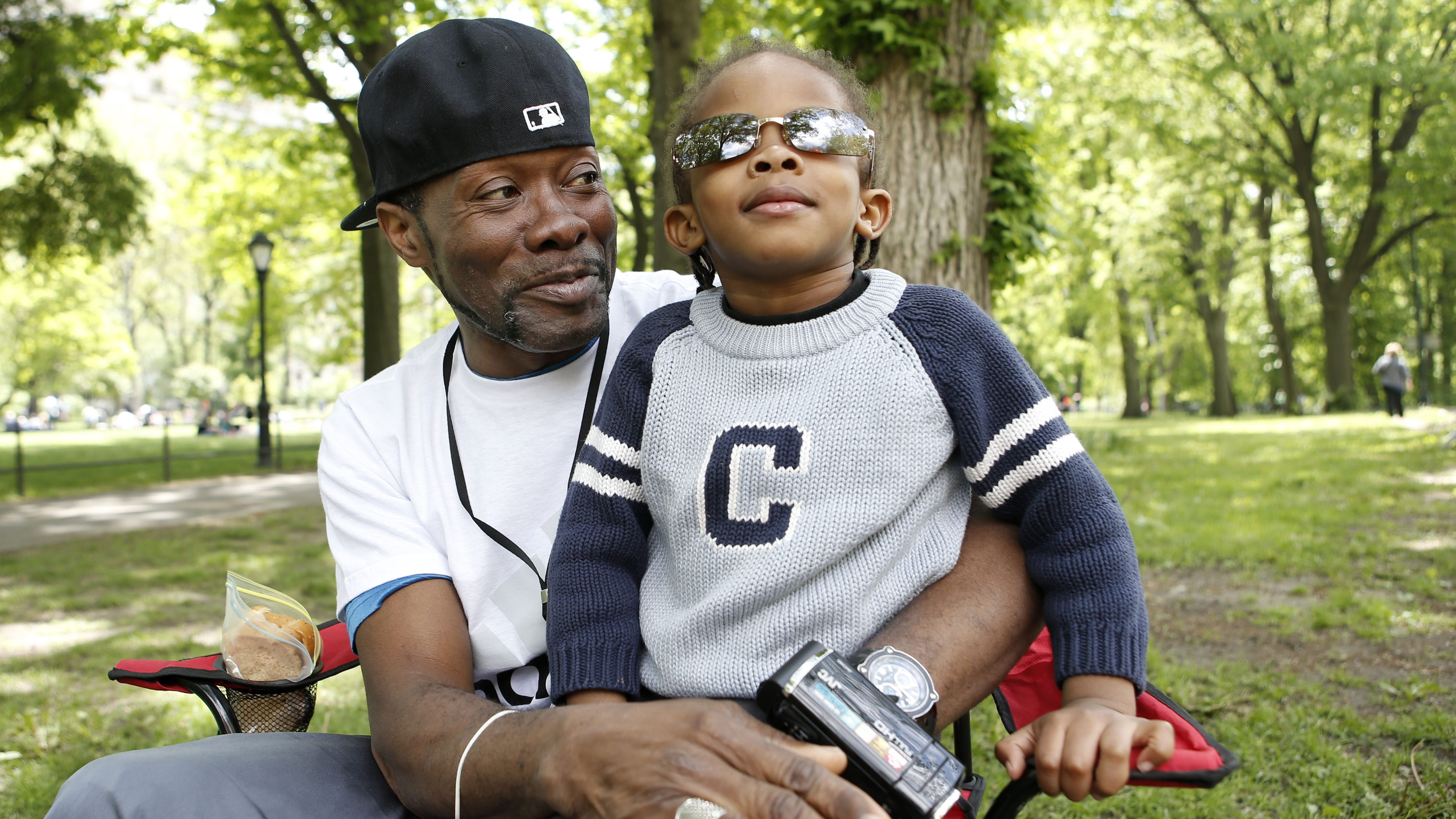 """FILE - In this May 18, 2014 photo, Jamez James, 47, of the Brooklyn borough of New York, holds his son, Melchi'Tzdec, during an outing in New York's Central Park. Before becoming a father, James said, """"I was a single guy, living the life, well, so I thought."""" James describes fatherhood as opening a door, and """"little did I know, as I chose to go through, my entire life changed... That's where I met my son, on the other side of the door."""" (AP Photo/Kathy Willens)"""