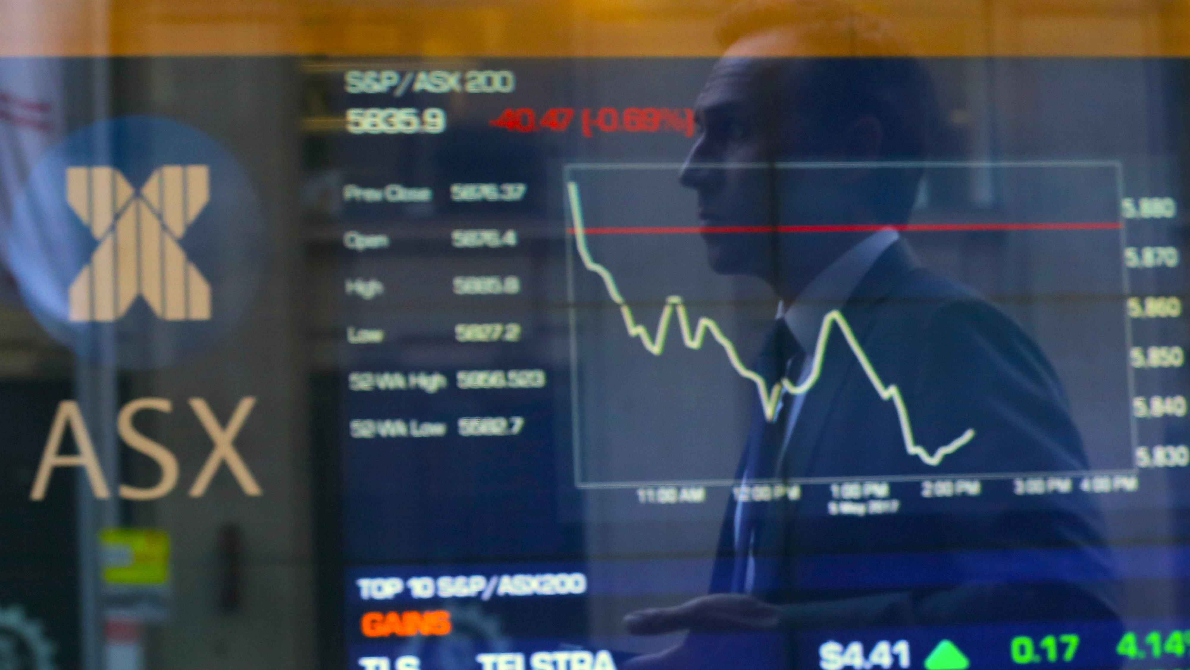 An investor is reflected in a window in front of a board displaying stock prices at the Australian Securities Exchange (ASX) in Sydney, Australia May 5, 2017