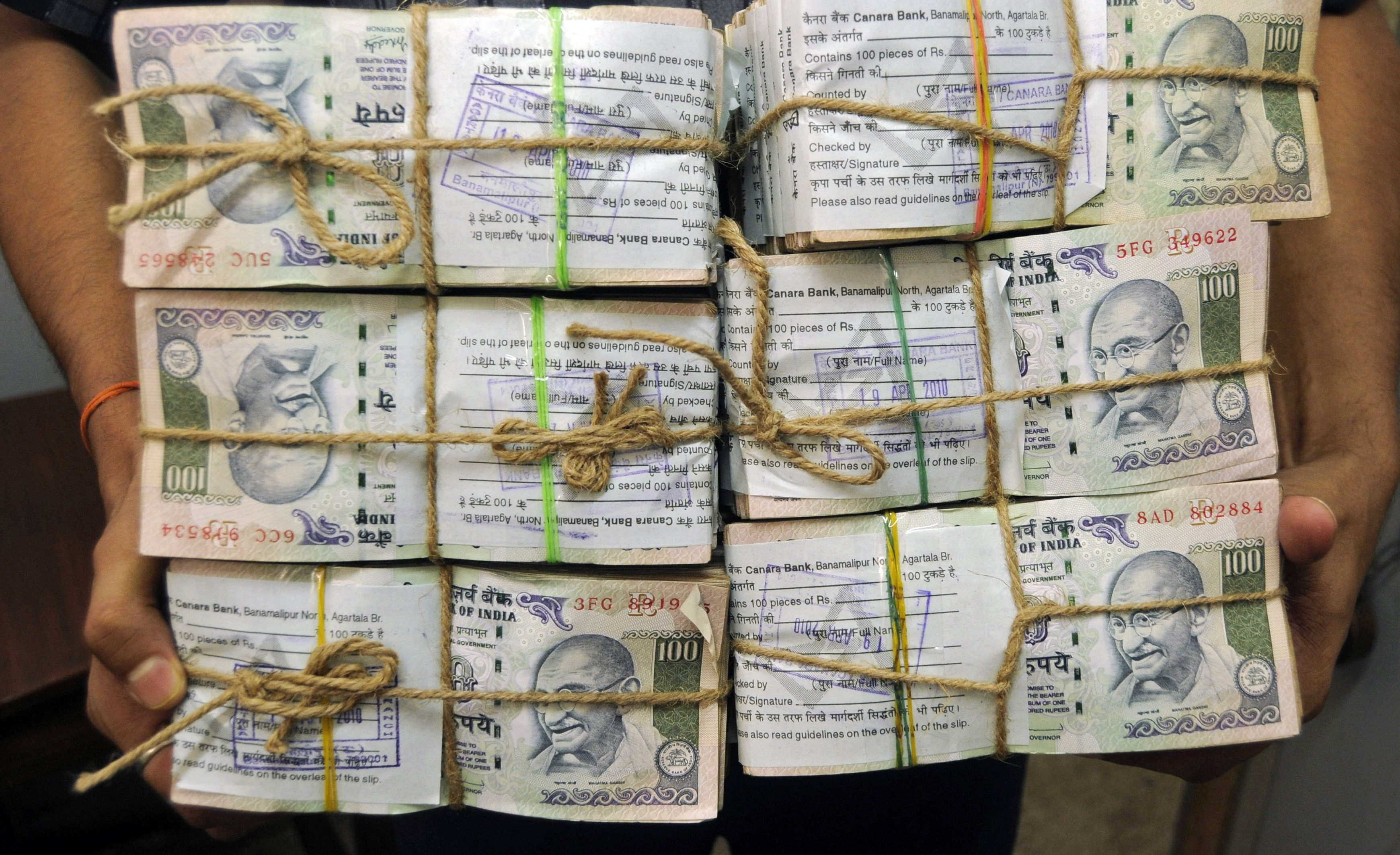 Bundles of Indian currency notes being carried around inside a bank in Agartala, Tripura.