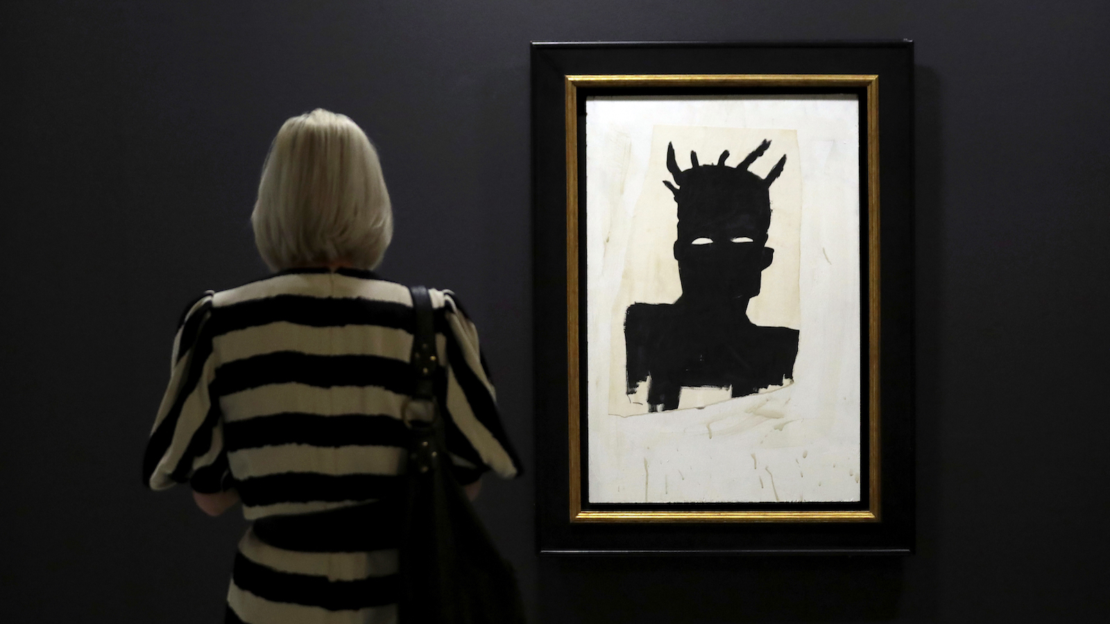 """The oil on paper and wood """"Self Portrait 1983"""" is displayed at the media view for """"Basquiat: Boom for Real"""", the first large-scale exhibition in the UK of the work of American artist Jean-Michel Basquiat at the Barbican Art Gallery in London, Wednesday, Sept. 20, 2017. Over 100 works are displayed in the exhibition from the artist who came of age in the late 1970s underground art and graffiti scene in New York and died aged 27 in 1988. (AP Photo/Matt Dunham)"""