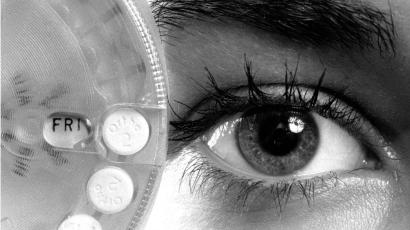 A birth control wheel held up to a face with mascara on the eye lid.