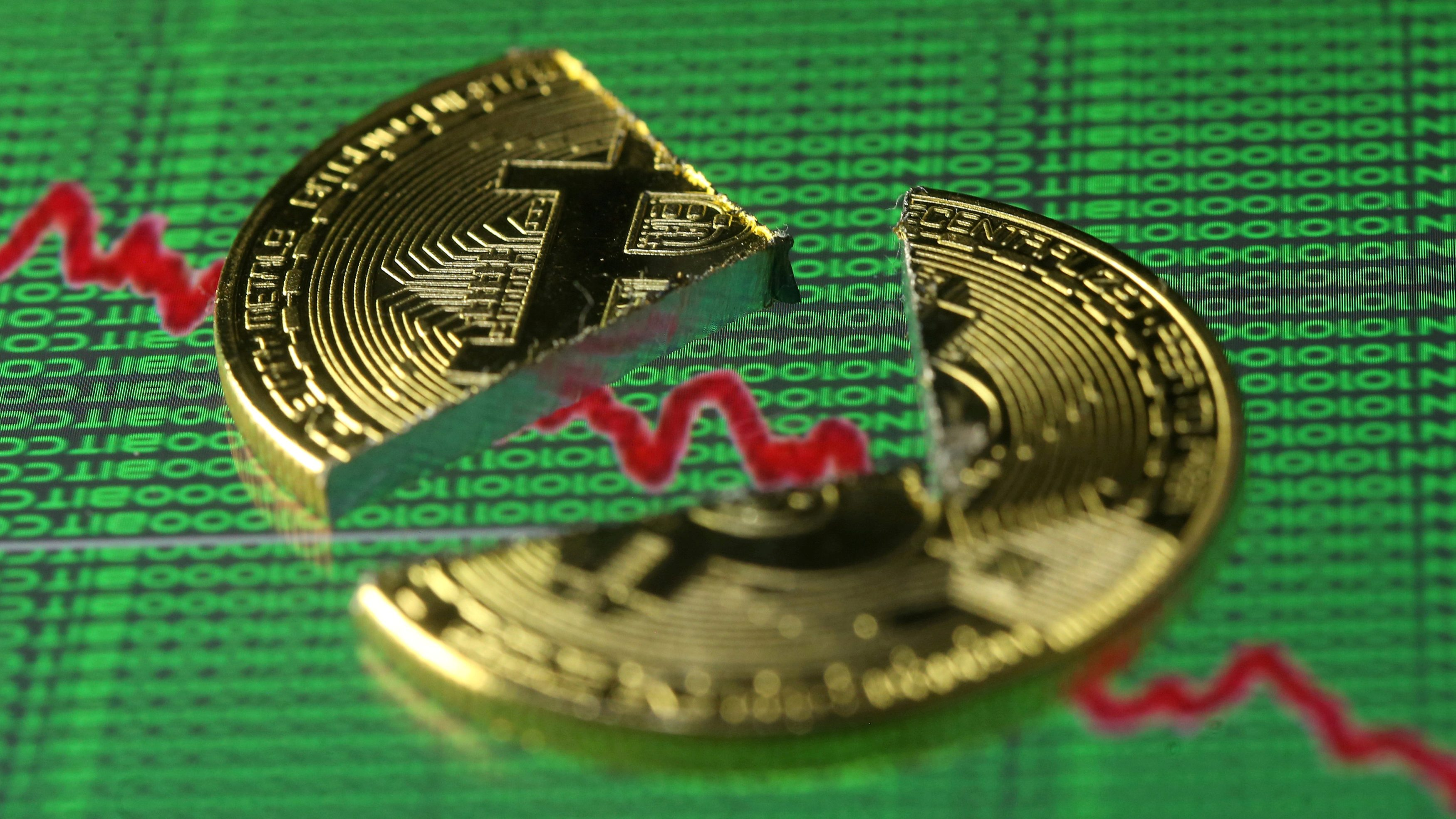 FILE PHOTO: Broken representation of the Bitcoin virtual currency, placed on a monitor that displays stock graph and binary codes, are seen in this illustration picture, December 21, 2017.