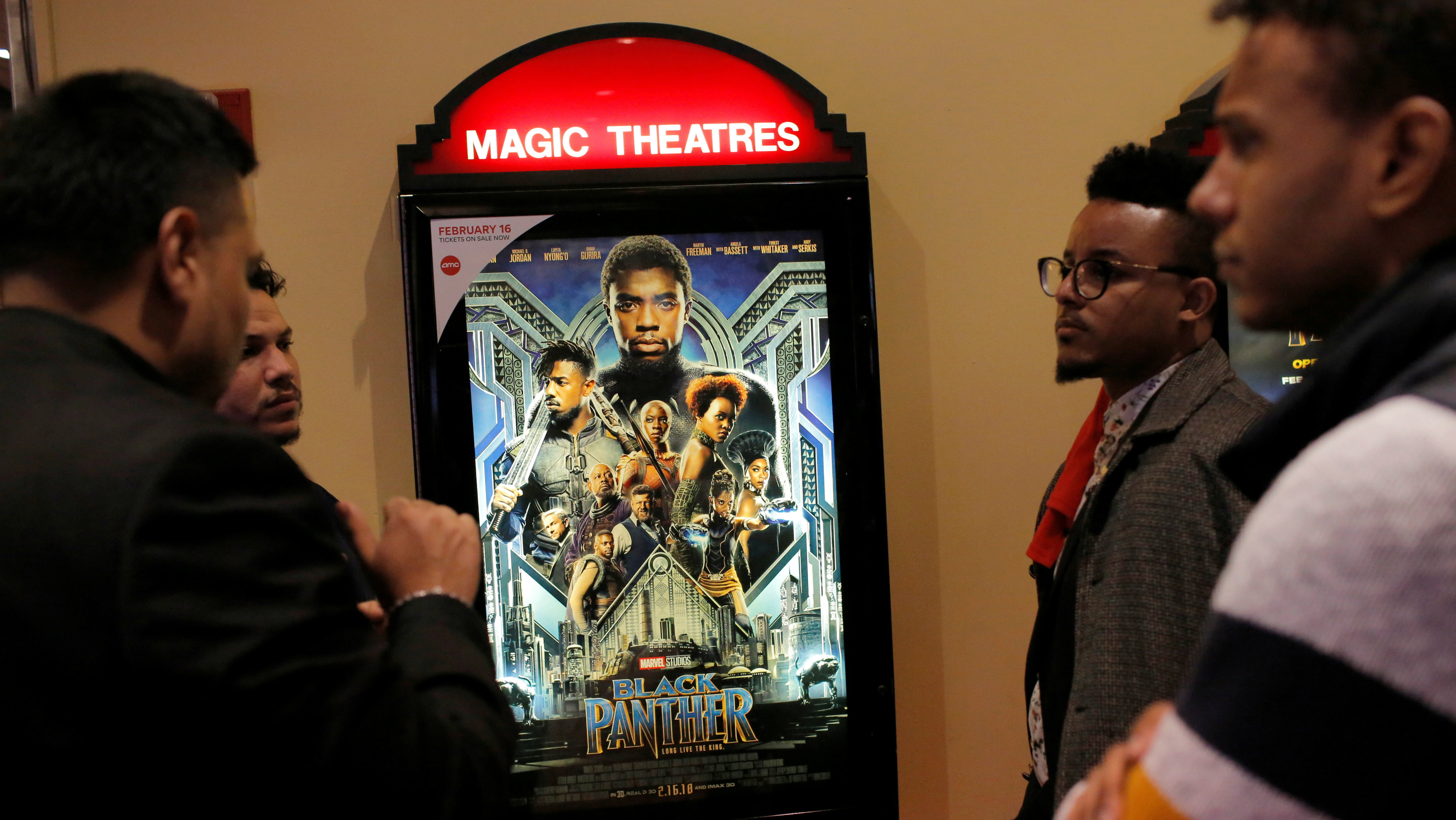 """A group of men gather in front of a poster advertising the film """"Black Panther"""" on its opening night of screenings at the AMC Magic Johnson Harlem 9 cinemas in Manhattan, New York, U.S., February 15, 2018."""