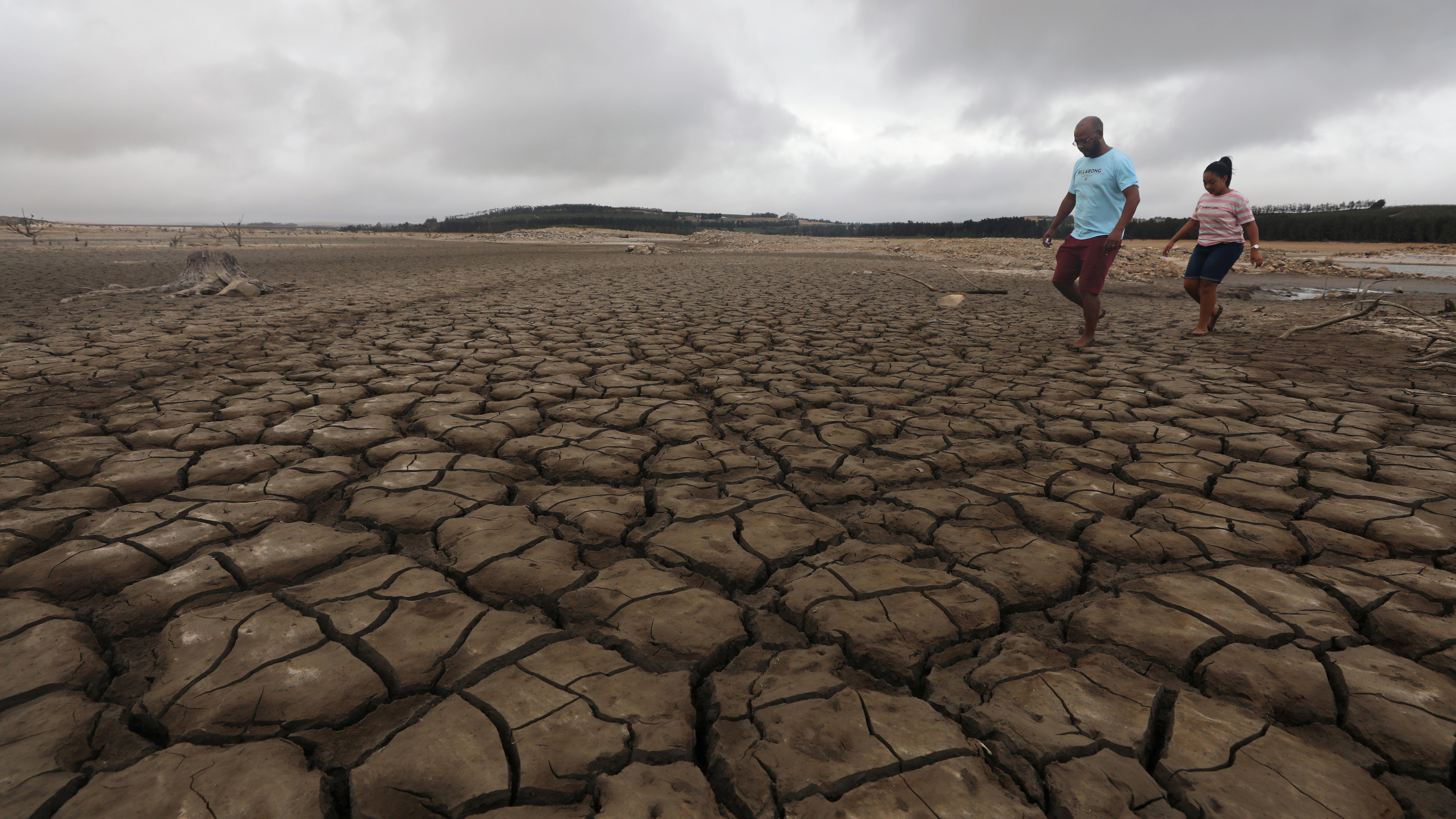 """A family negotiates their way through caked mud around a dried up section of the Theewaterskloof dam near Cape Town, South Africa, January 20, 2018. The dam, which supplies most of Cape Town's potable water, is currently dangerously low as the city faces """"Day Zero"""", the point at which taps will be shut down accross the city.  Picture taken January 20, 2018. REUTERS/Mike Hutchings - RC176FA9C1B0"""