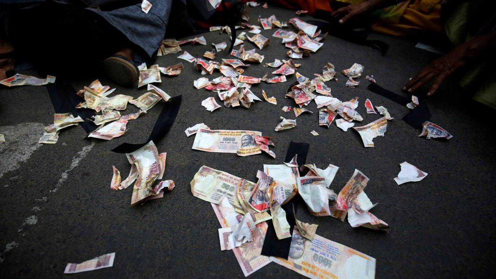 Pieces of old fake 1000 rupee notes lay on the street during a protest, organised by India's main opposition Congress party, to mark a year since demonetisation was implemented by Prime Minister Narendra Modi, in Ahmedabad, India November 8, 2017.