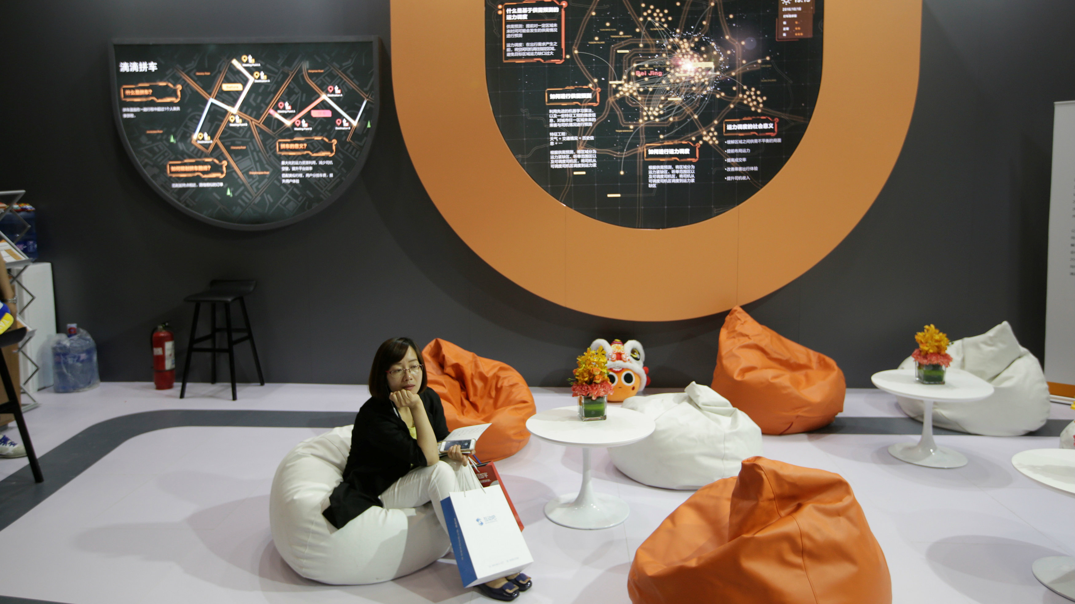 A woman sits at Didi Chuxing's booth at the Global Mobile Internet Conference (GMIC) 2017 in Beijing, China