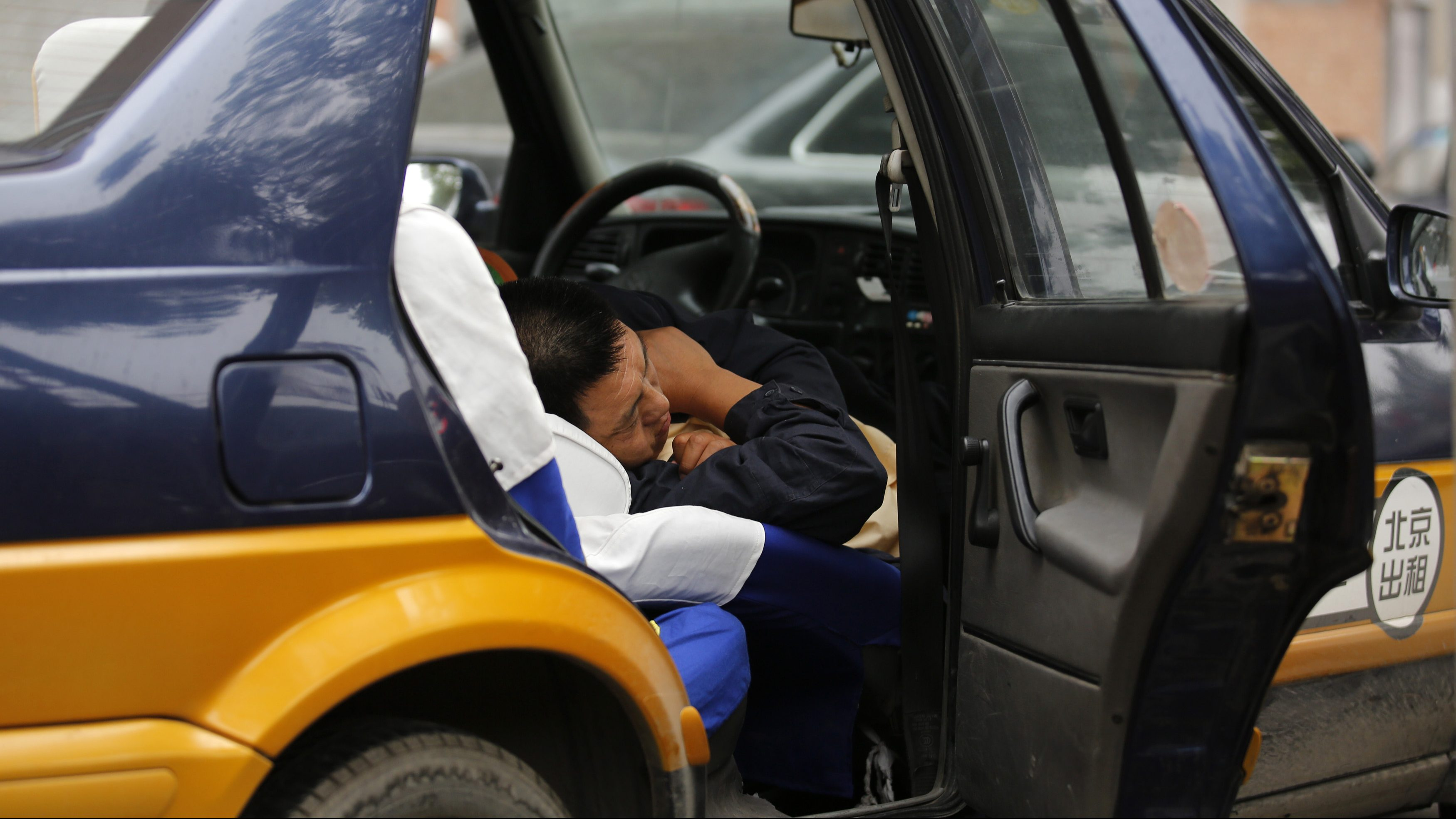 A taxi driver take a nap inside the taxi in Beijing June 6, 2013. Activity in China's services sector expanded in May but at a pace little changed from the month before, the latest sign that the world's No. 2 economy is struggling to regain momentum. REUTERS/Kim Kyung-Hoon (CHINA - Tags: BUSINESS) - GM1E9661D4601