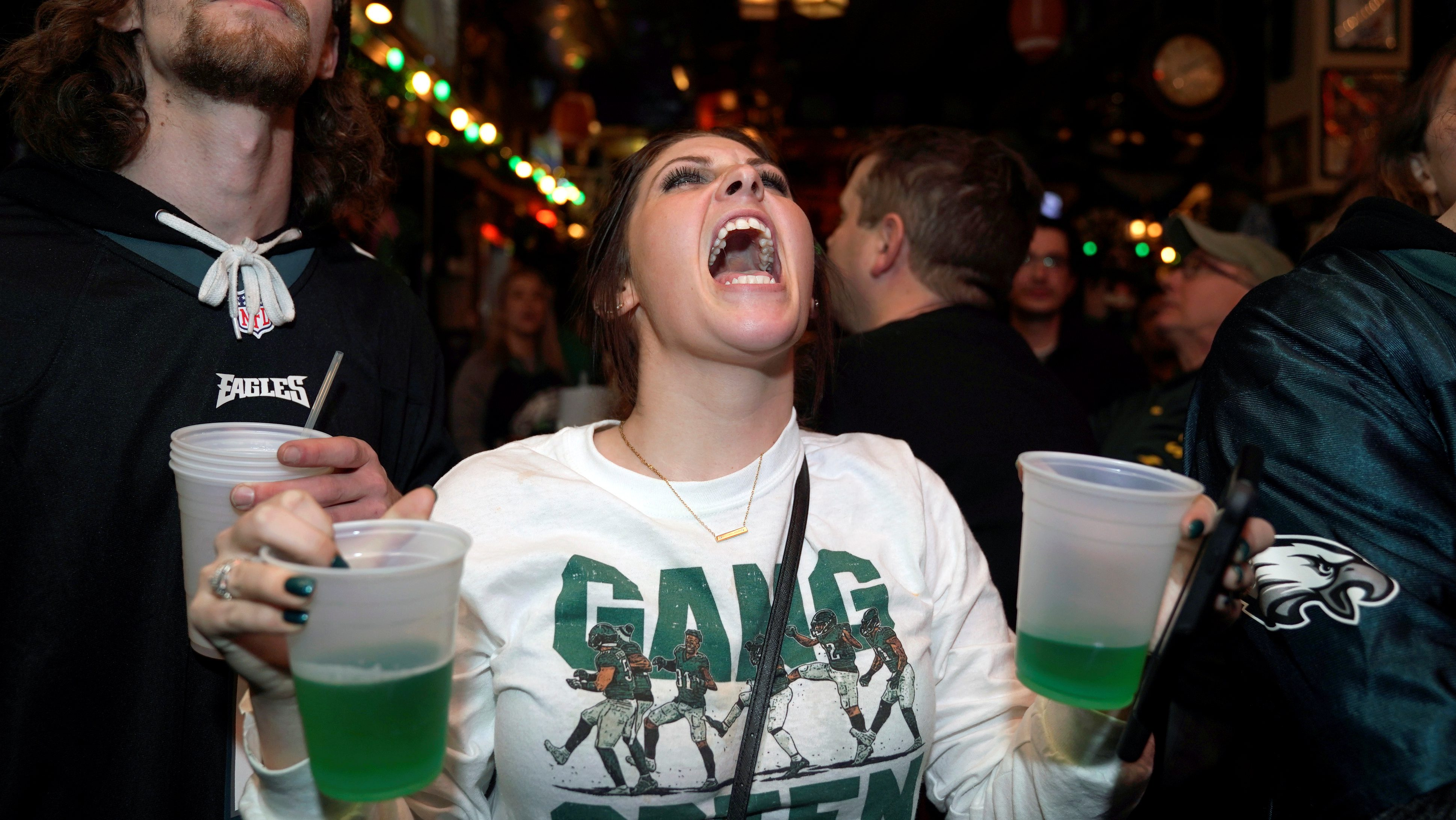 Football fans, Nicholas Breslin (L) and Laura Demutis, react as they watch Super Bowl LII between the New England Patriots and the Philadelphia Eagles at the city's oldest tavern, McGillin's Olde Ale House in Philadelphia, Pennsylvania, U.S. February 4, 2018.