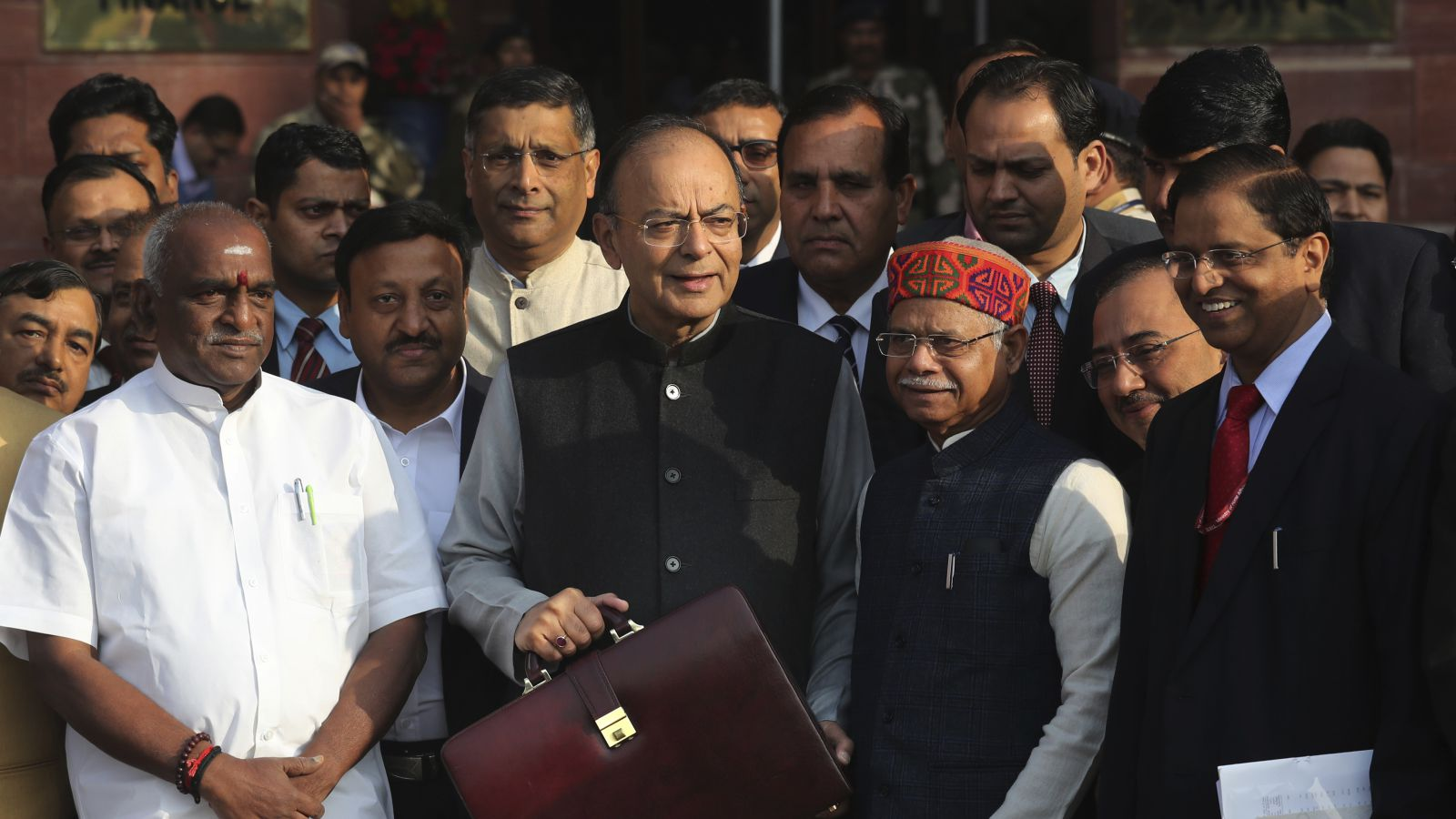 Indian Finance Minister Arun Jaitley, center, holds a briefcase containing federal budget documents leaves for parliament house with Junior Finace minsters Shiv Pratap Shukla, center right, and Pon Radhakrishnan, left, from his office in New Delhi, India, in New Delhi, India, Thursday, Feb. 1, 2018. Jaitley is expected to announce populist giveaways in an attempt to woo voters as this is the last budget of Indian Prime Minister Narendra Modi's government which will seek a second five-year tenure in May 2019 national elections.