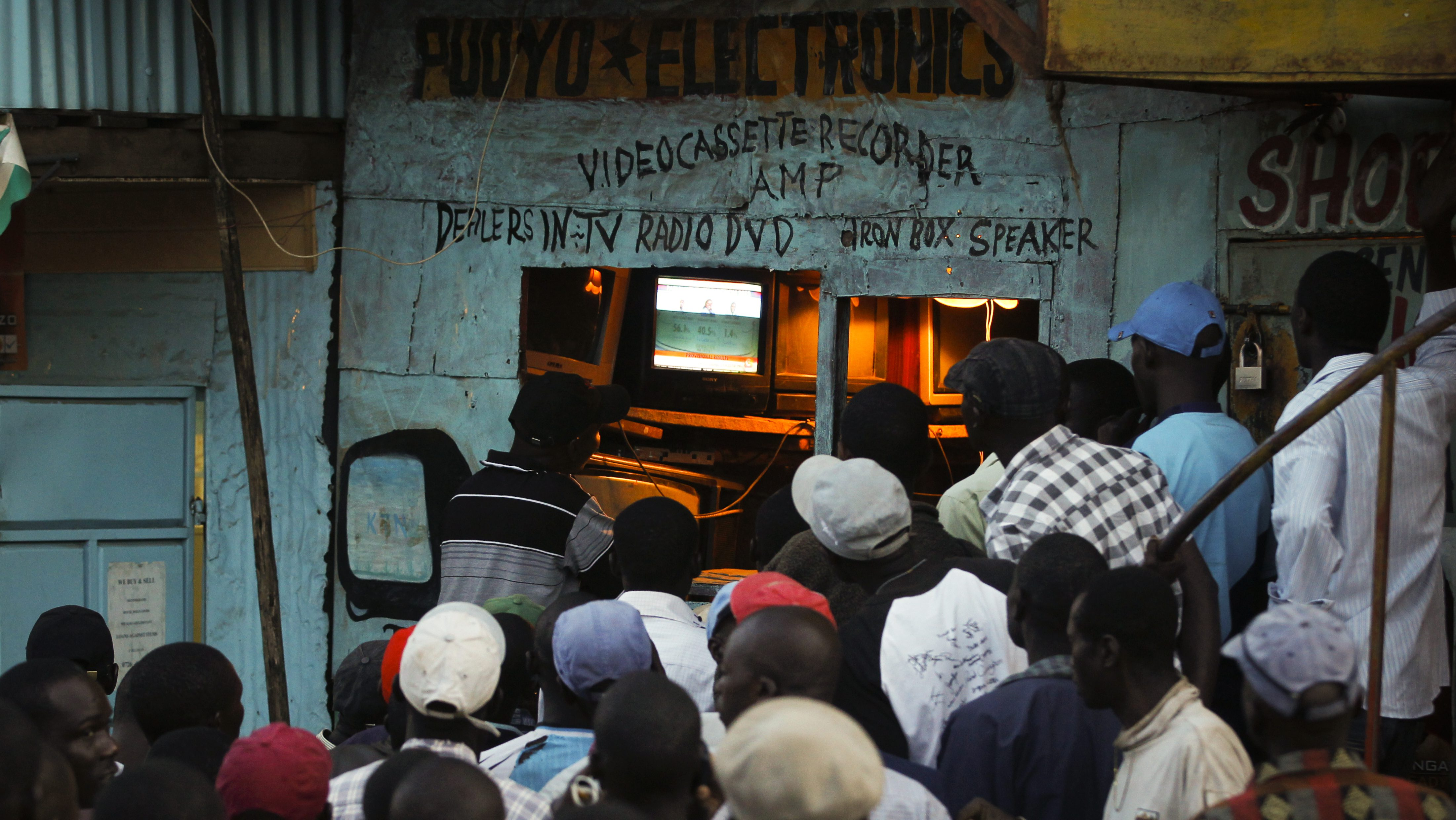 People follow the news on television as the provisional results are slowly being revealed at an electronics shop in the Kibera slum, Nairobi, Kenya, 05 March 2013. Provisional result announced on 05 March show the Deputy Prime Minister Uhuru Kenyatta ahead of Prime Minister Raila Odinga.