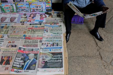 A Kenyan newspaper vendor (R) reads a newspaper featuring front page article about US President-elect Donald Trump as he waits for customers at a street in Nairobi, Kenya, 10 November 2016. Americans on 08 November chose Republican candidate Donald Trump as the 45th President of the United States of America, to serve from 2017 through 2020.