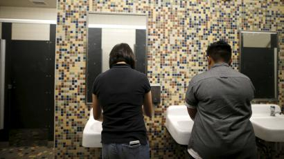Two people washing their hands in a bathroom.