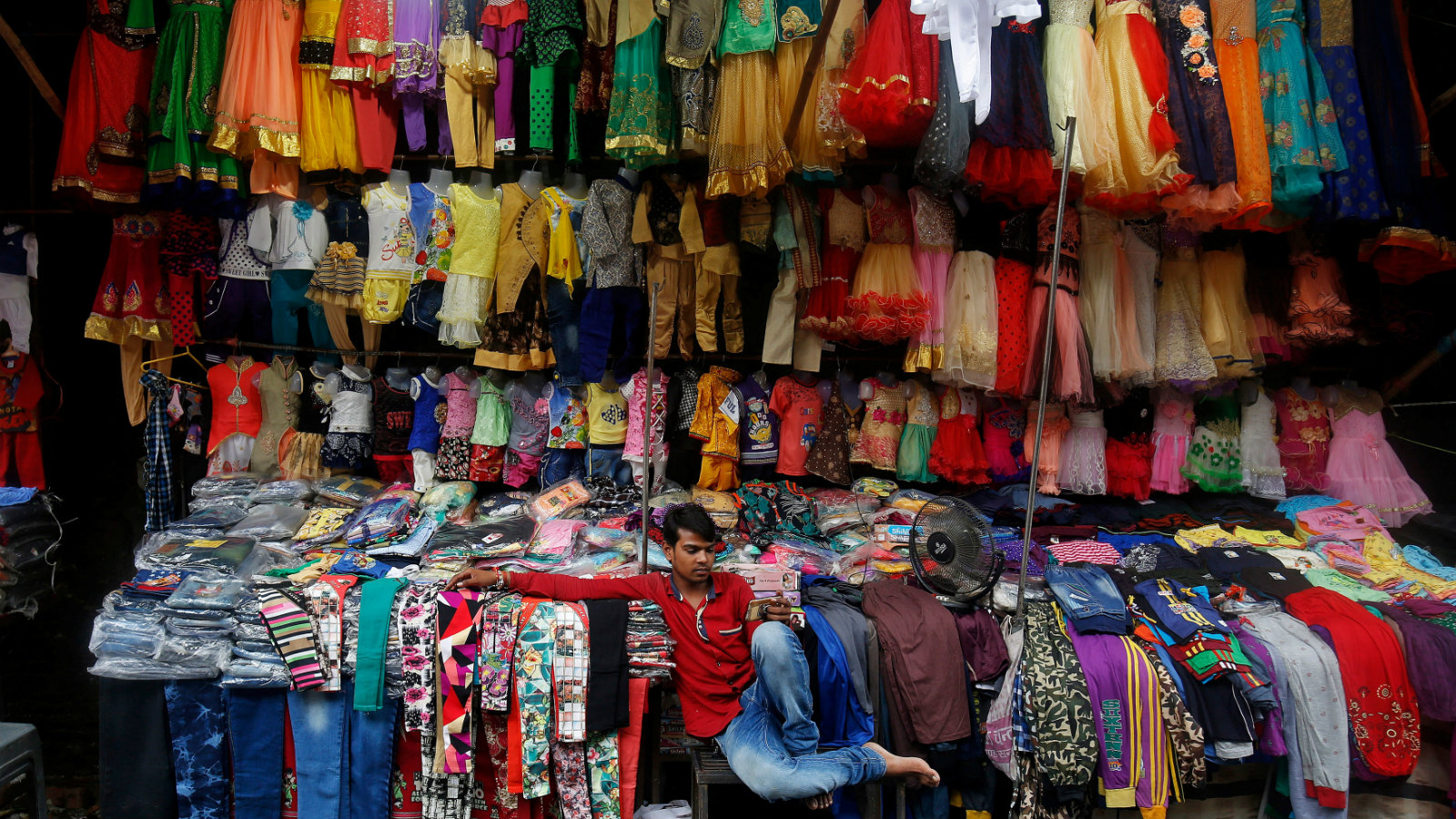 A costume vendor checks his mobile phone as he waits for customers in Rishikesh, India, August 10, 2017.