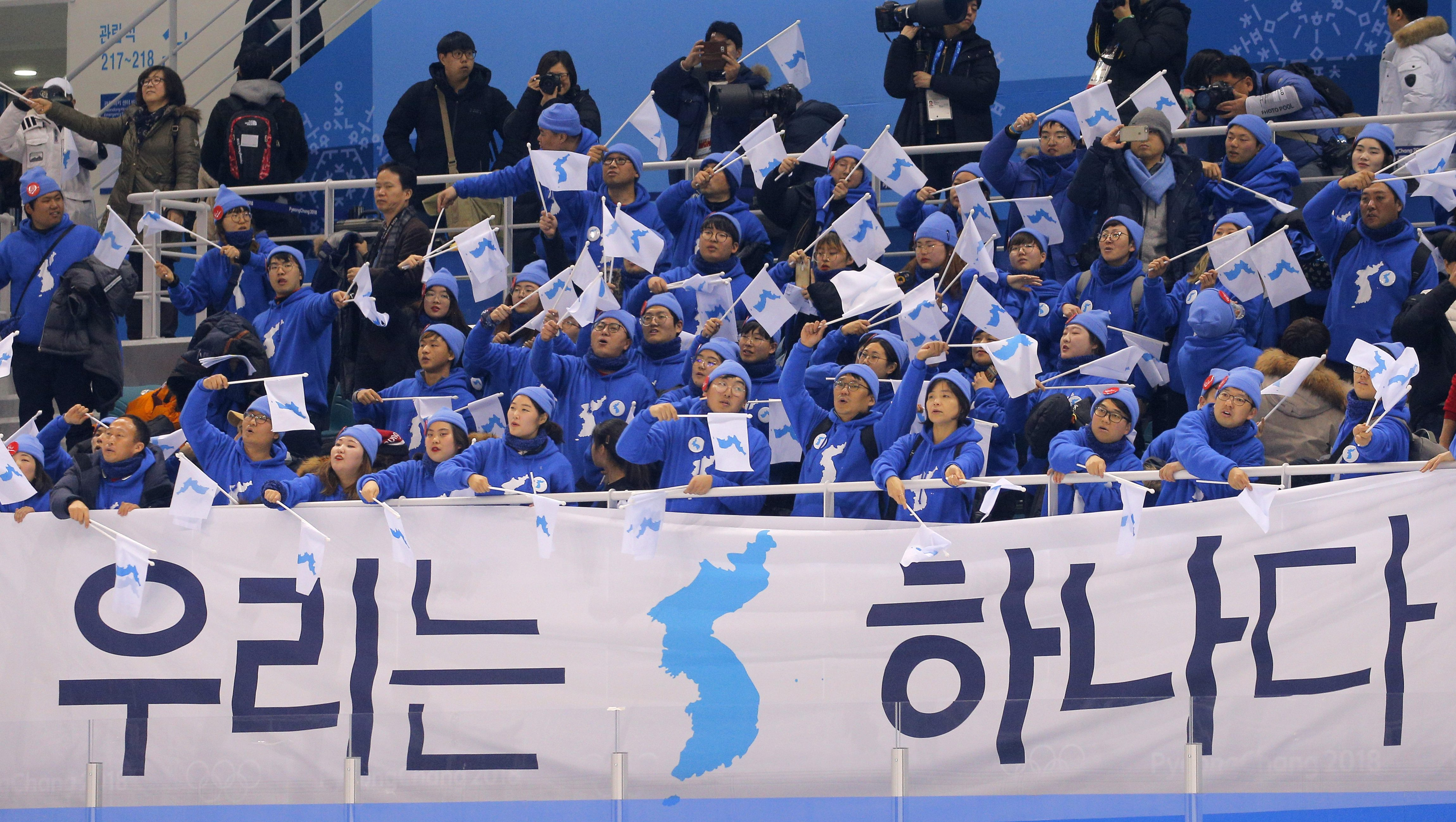 "Ice Hockey – Pyeongchang 2018 Winter Olympics – Women Preliminary Round Match - Sweden v Korea - Kwandong Hockey Centre, Gangneung, South Korea – February 12, 2018 - Fans wave Korea Unification flags behind a banner that reads ""We are one""."