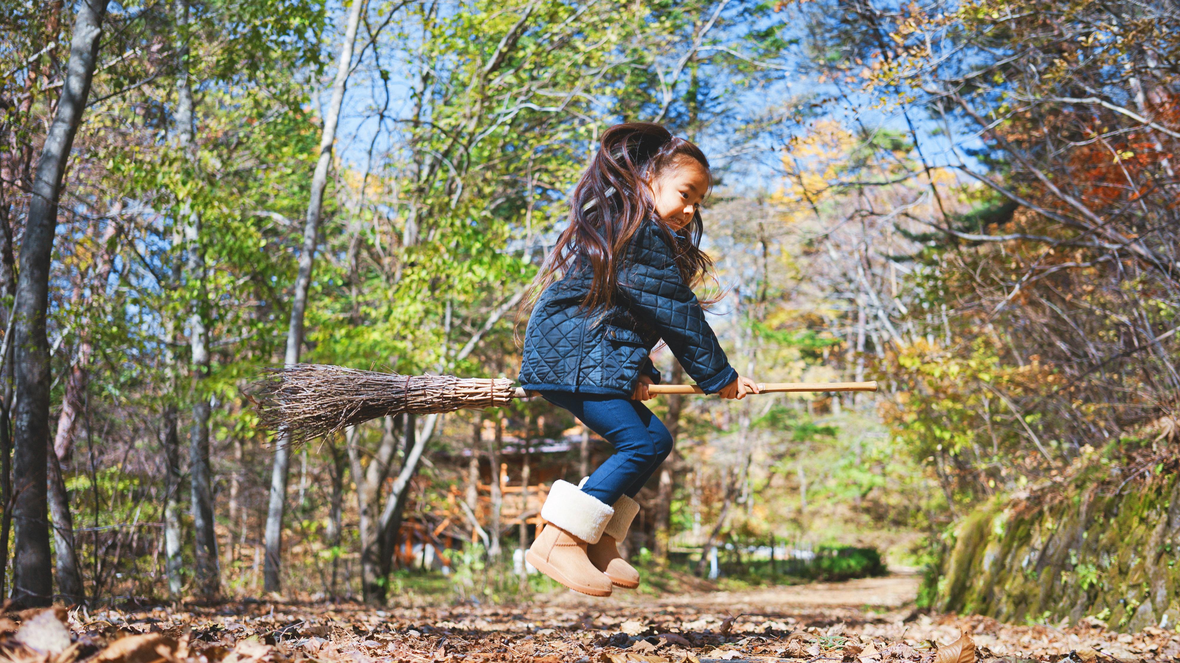 Child playing on broom.