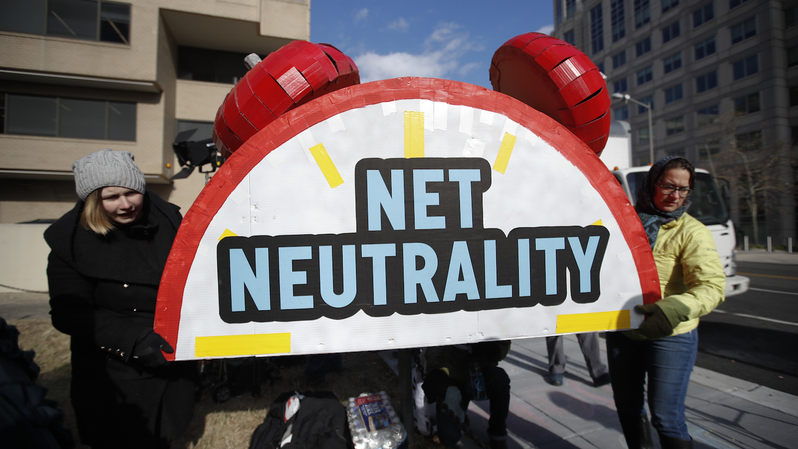 """Sammi LeMaster, left, and Katherine Fuchs, right, carry the top of an alarm clock display that reads """"Net Neutrality"""" after a protest at the Federal Communications Commission (FCC) in Washington, Thursday, Dec. 14, 2017, where the FCC is scheduled to meet and vote on net neutrality. The vote scheduled today at the FCC, could usher in big changes in how Americans use the internet, a radical departure from more than a decade of federal oversight. (AP Photo/Carolyn Kaster)"""