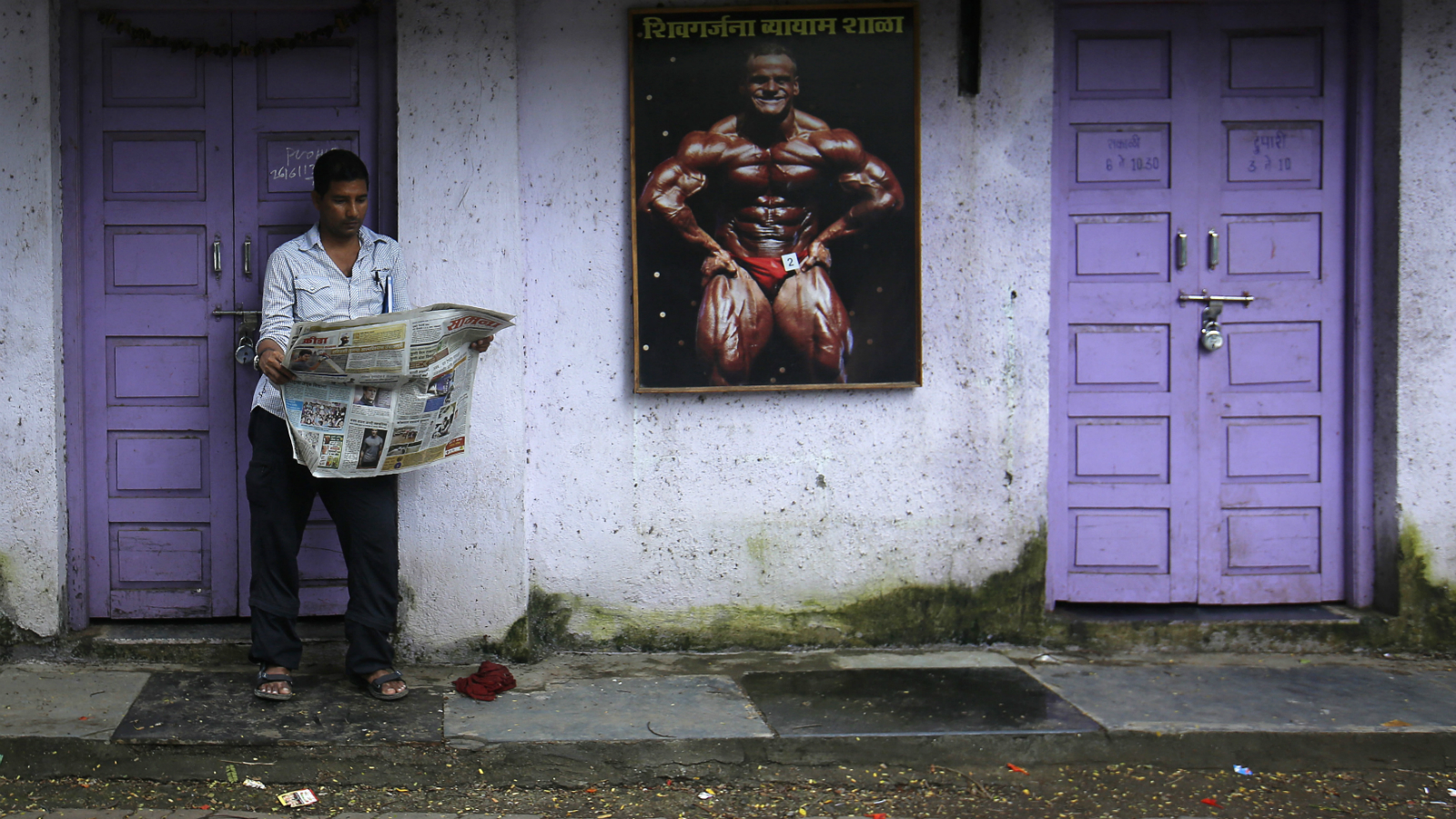 A man reads a newspaper outside a closed gym in Mumbai July 3, 2013. REUTERS/Danish Siddiqui