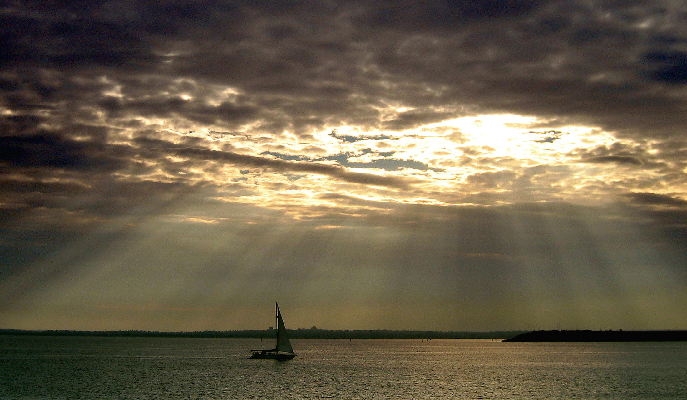 A boat sails on Sydney's Botany Bay as sun rays break through clouds November 10, 2004. Australia's weather is changing, weather scientists said at a climate and water forum this week, blaming growing clouds of carbon dioxide from industry, changes in Antarctic circulation because of ozone depletion and natural variability. The main scientific body in Australia, the Commonwealth Scientific and Industrial Research Organisation (CSIRO), has projected that by 2030 the average temperature in Australia will increase by two degrees celcius (35.6 Farenheit), and a change in rainfall of between plus five percent and minus 15 percent.