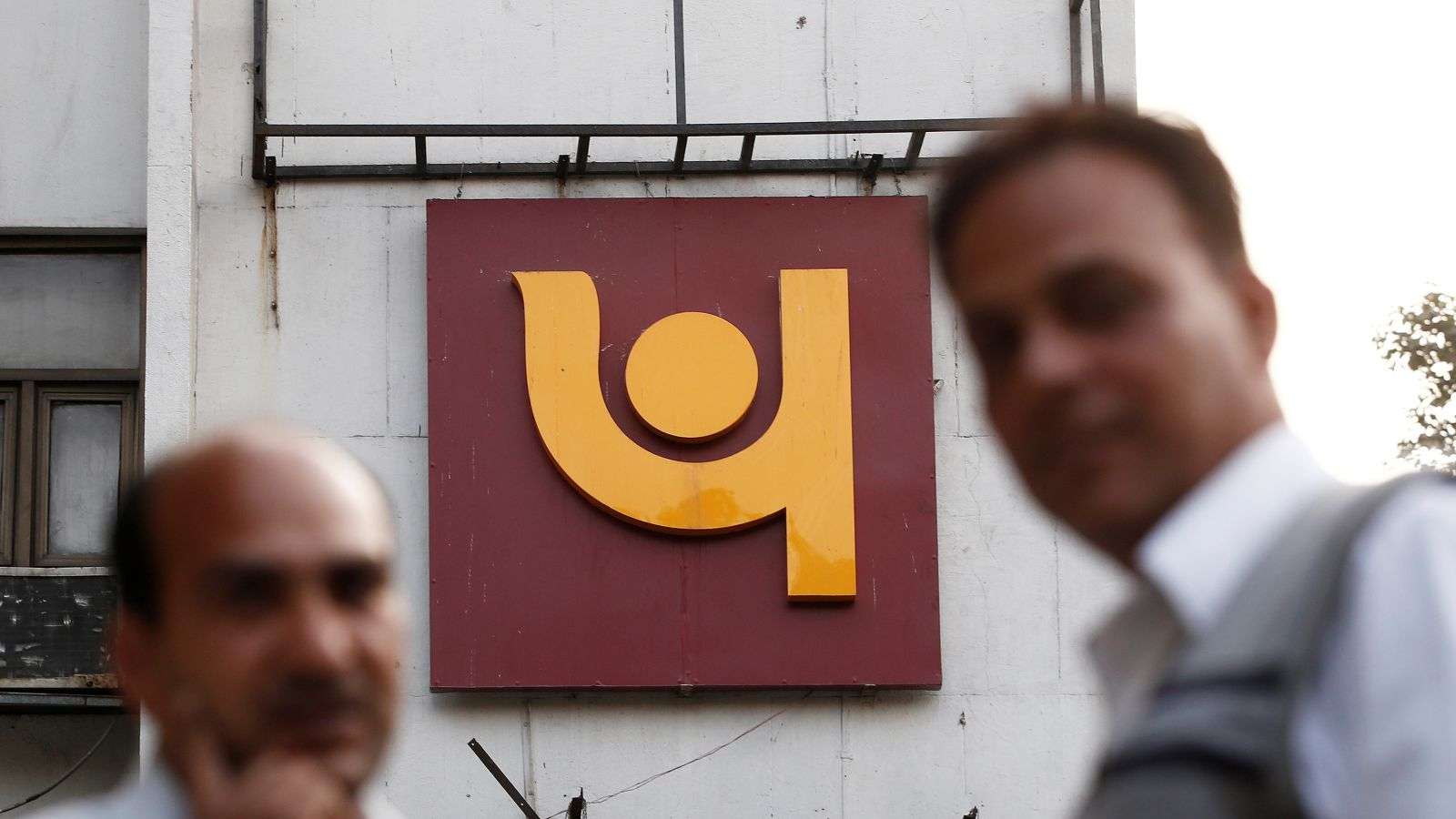 People stand in front of the logo of Punjab National Bank outside a branch of the bank in New Delhi, India February 15, 2018
