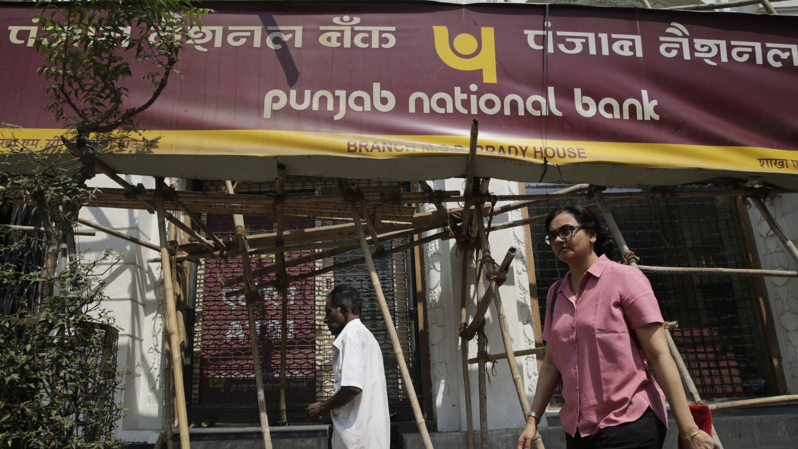 People walk pats a Punjab National Bank branch after it was sealed by the Central Bureau of Investigation in Mumbai, India, Monday, Feb. 19, 2018. Indian investigators on Friday ordered two wealthy jewelers to be questioned about an alleged $1.8 billion scam at the large state-owned bank, a news report said