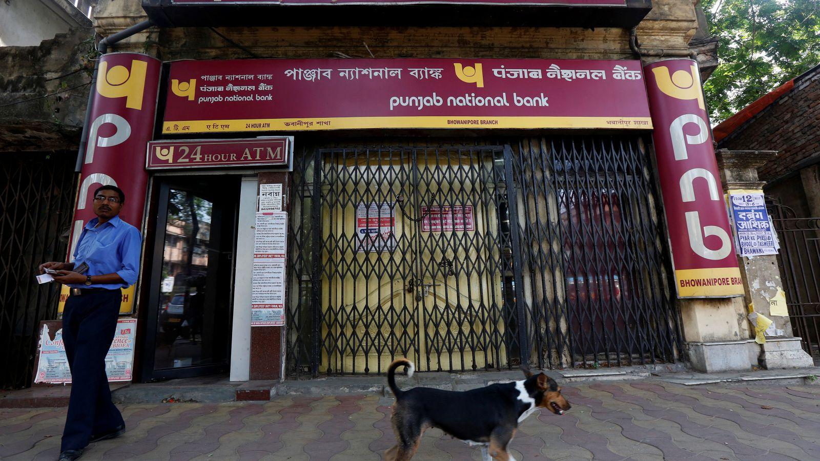 A man exits Punjab National Bank's building as a stray dog walks past in Kolkata, India May 16, 2017