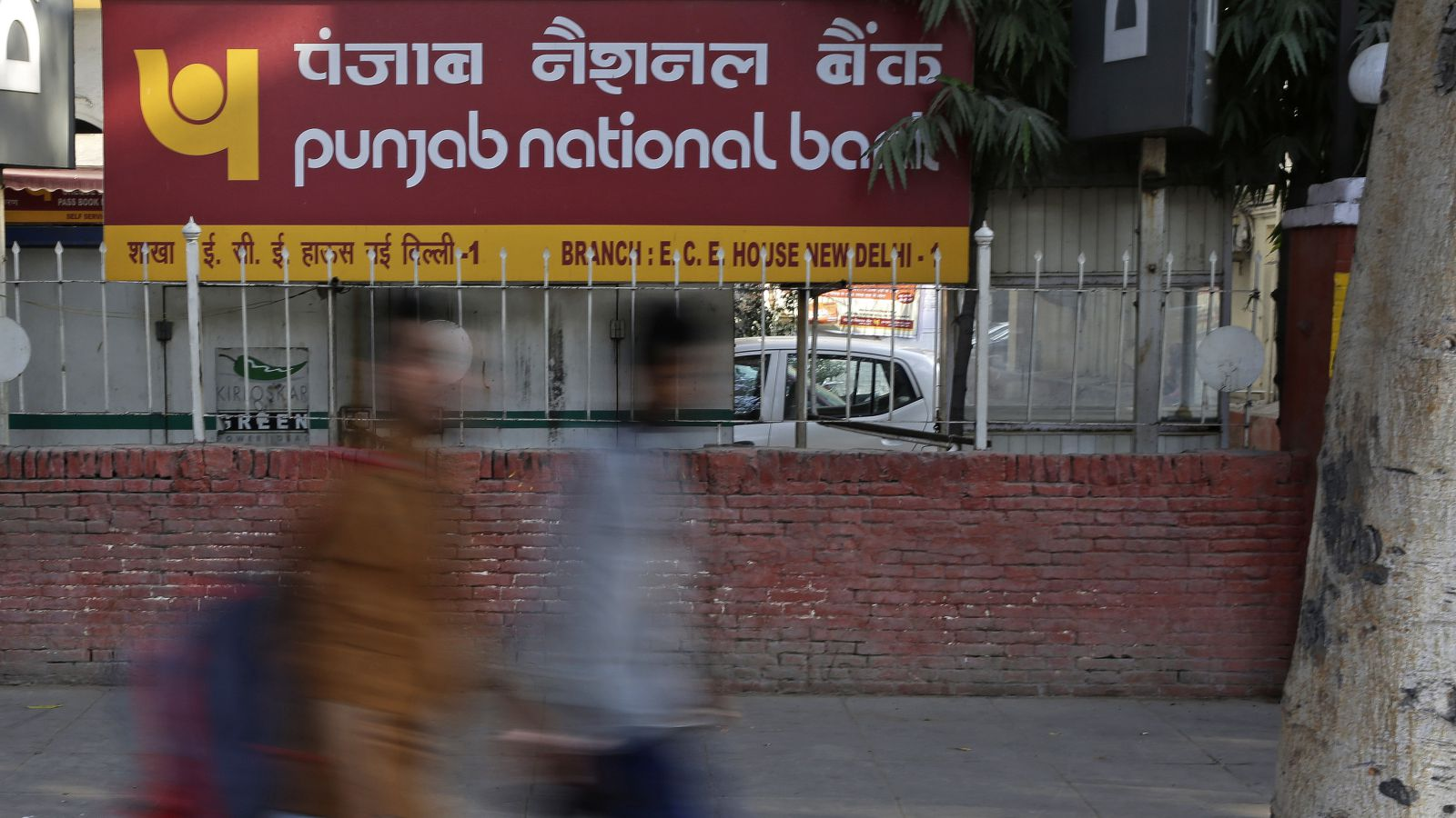 Pedestrians walk past a sign board of Punjab National Bank in New Delhi, India, Thursday, Feb. 15, 2018. State-owned Punjab National Bank has said in a statement that fraudulent transactions totaling $1.8 billion had been discovered in a Mumbai bank branch. Indian media outlets have linked the scam to jeweler Nirav Modi.