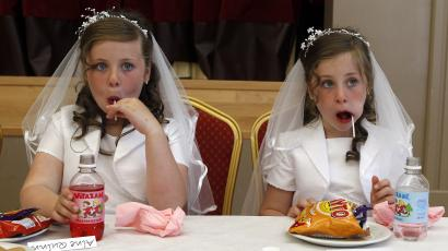 Twins Aine (L) and Emer Quinn eat sweets in the local parish hall in Cushendall